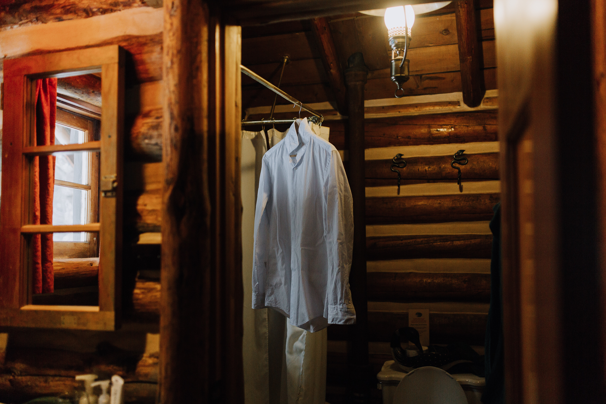 Grooms shirt hanging in cosy log cabin at Storm Mountain Lodge winter wedding