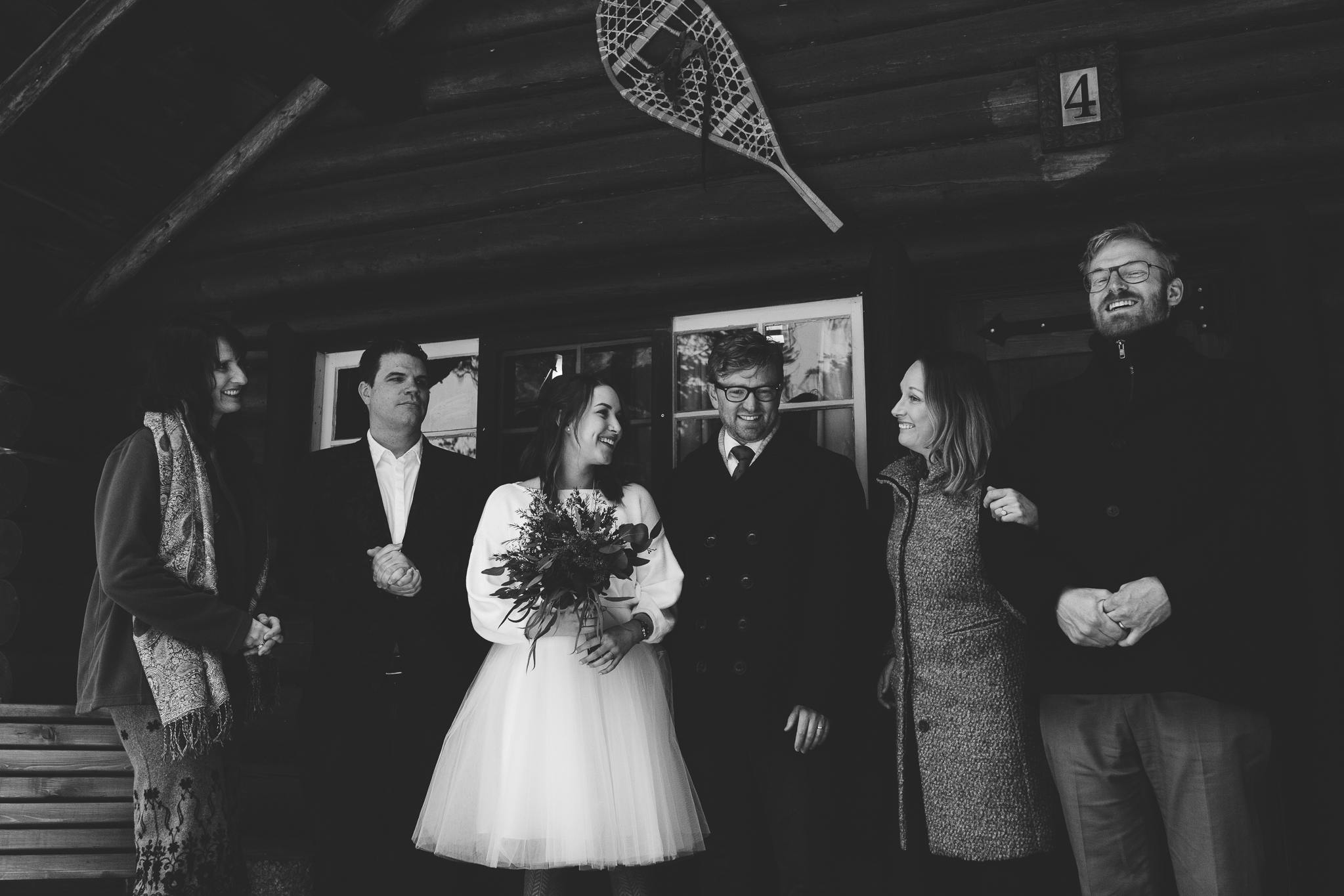 Bride and groom and witnesses on log cabin porch during winter wedding at Storm Mountain Lodge, Banff
