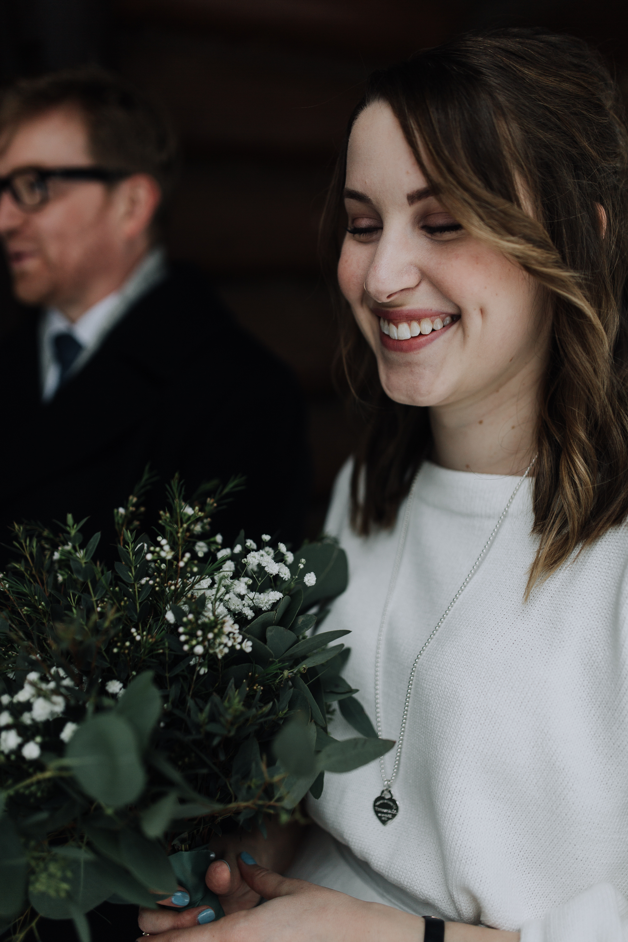 Close up of bride holding greenery bouquet during winter wedding at Storm Mountain Lodge Banff