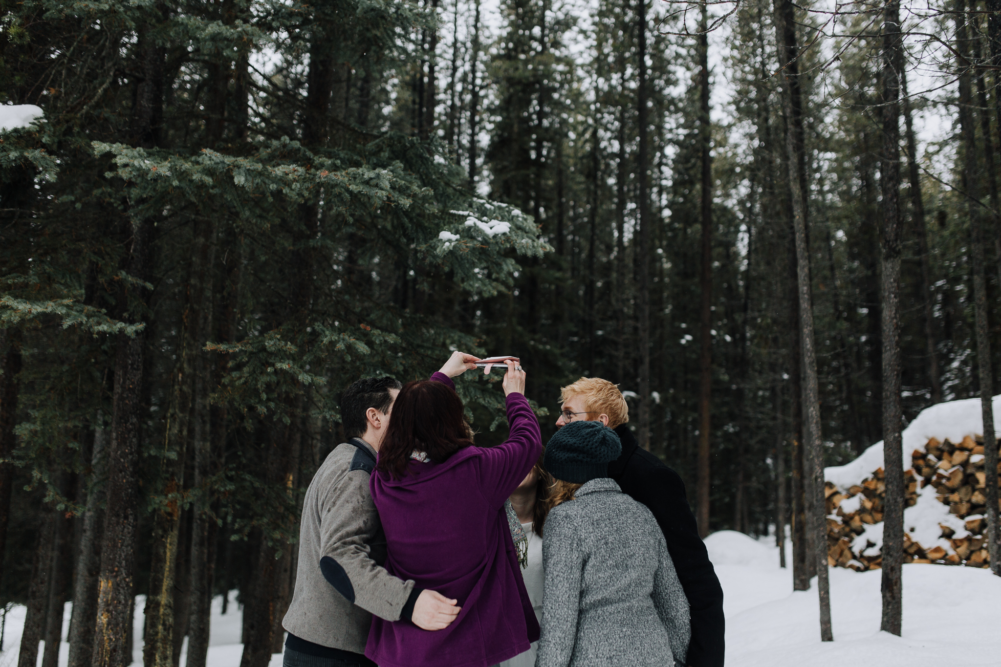 Guests taking selfie in the woods at Storm Mountain Lodge winter wedding, Banff