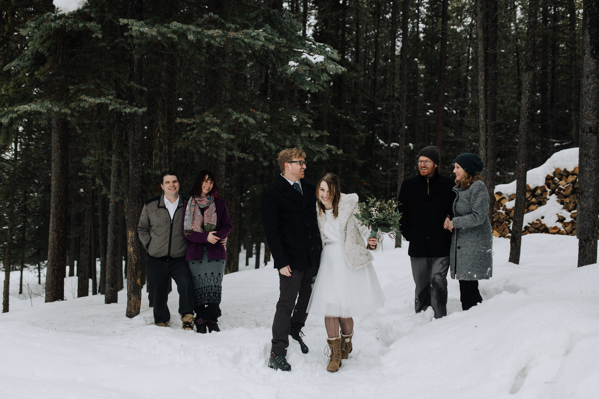 Wedding party standing in snow at Storm Mountain Lodge winter wedding, Banff