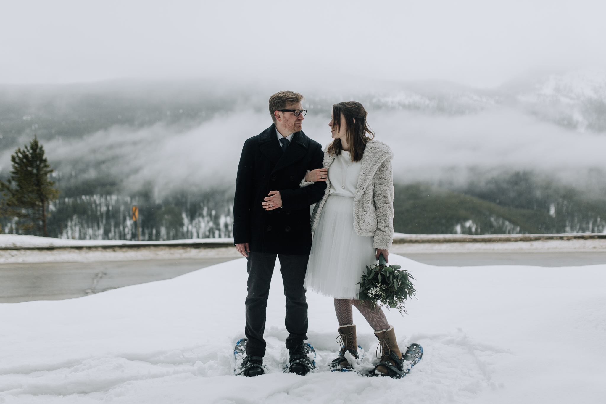 Bride and groom wearing snowshoes linking arms with mountains of Banff National Park in the background