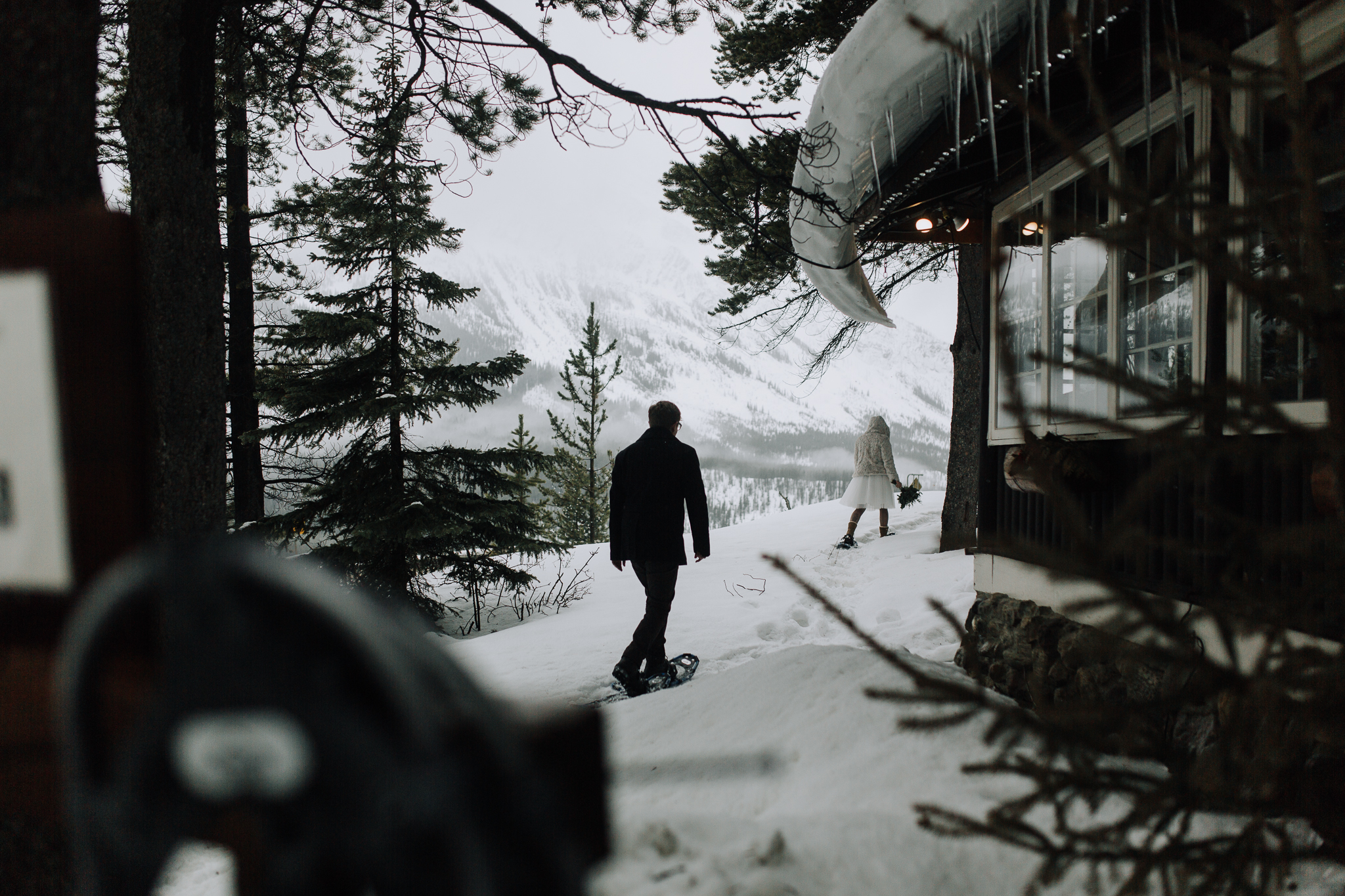Bride and groom snowshoeing in Banff National Park after intimate wedding