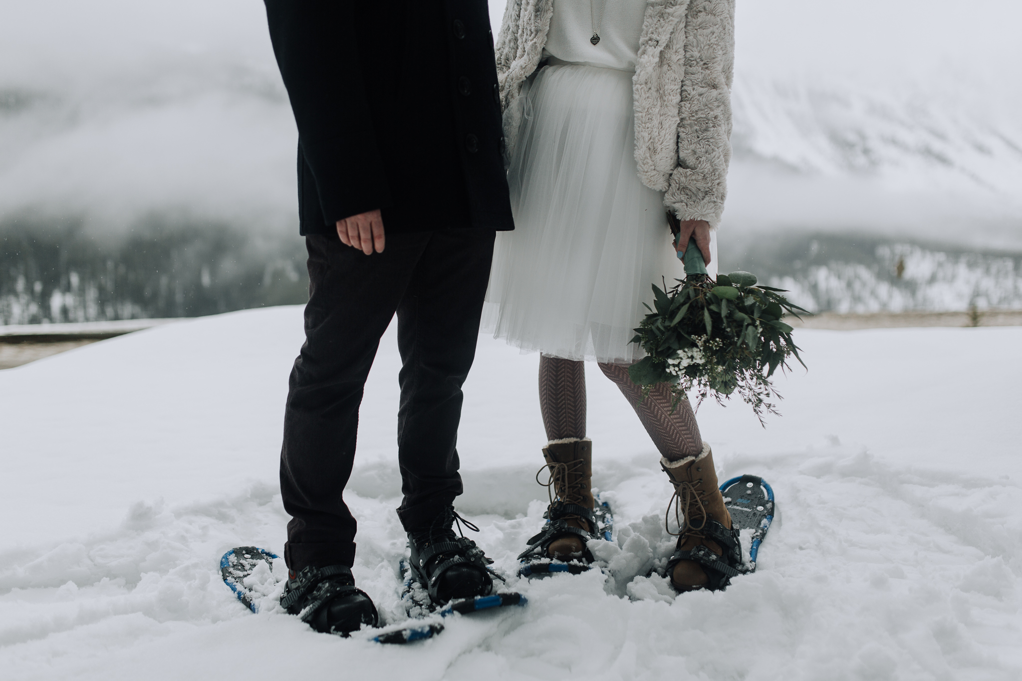 Photo of bride and groom wearing snowshoes and tulle skirt holding bouquet at Storm Mountain Lodge