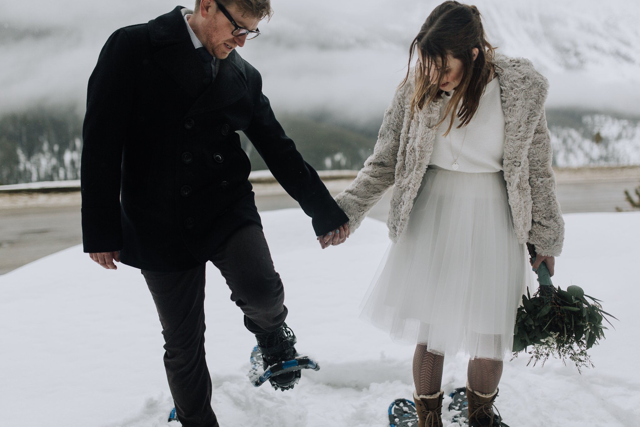 Bride and groom wearing snowshoes for intimate wedding photos at Storm Mountain Lodge