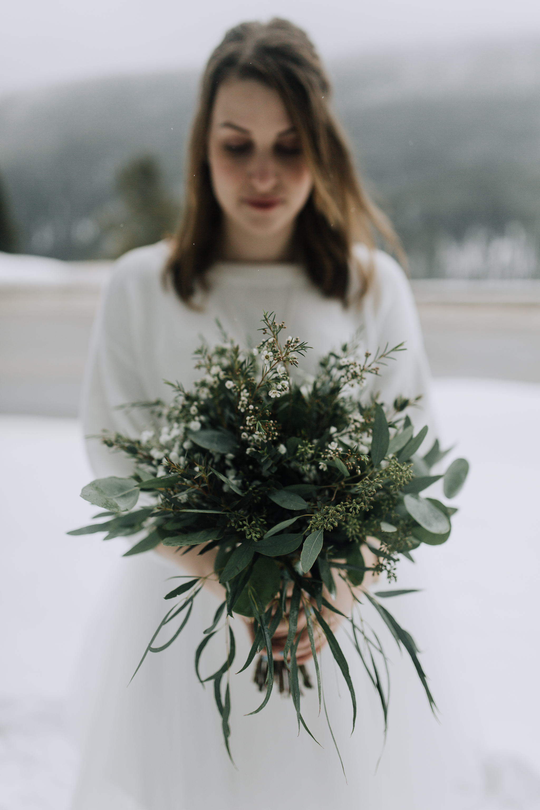 Bride standing in snow holding greenery bouquet after intimate elopement at Emerald Lake Lodge