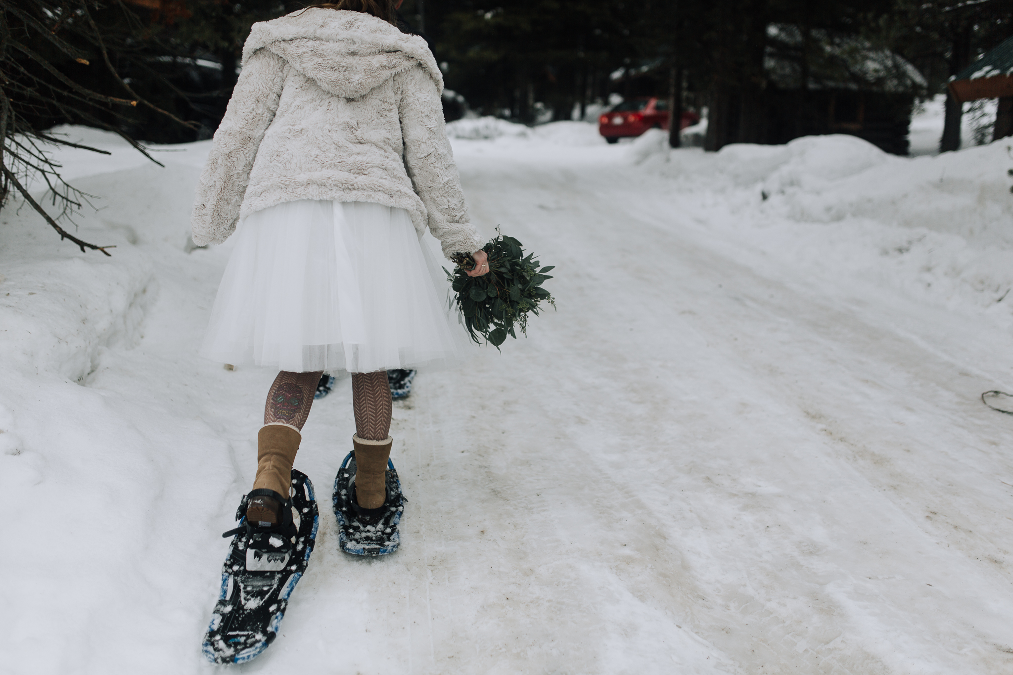 Bride snowshoeing during intimate elopement at Emerald Lake Lodge