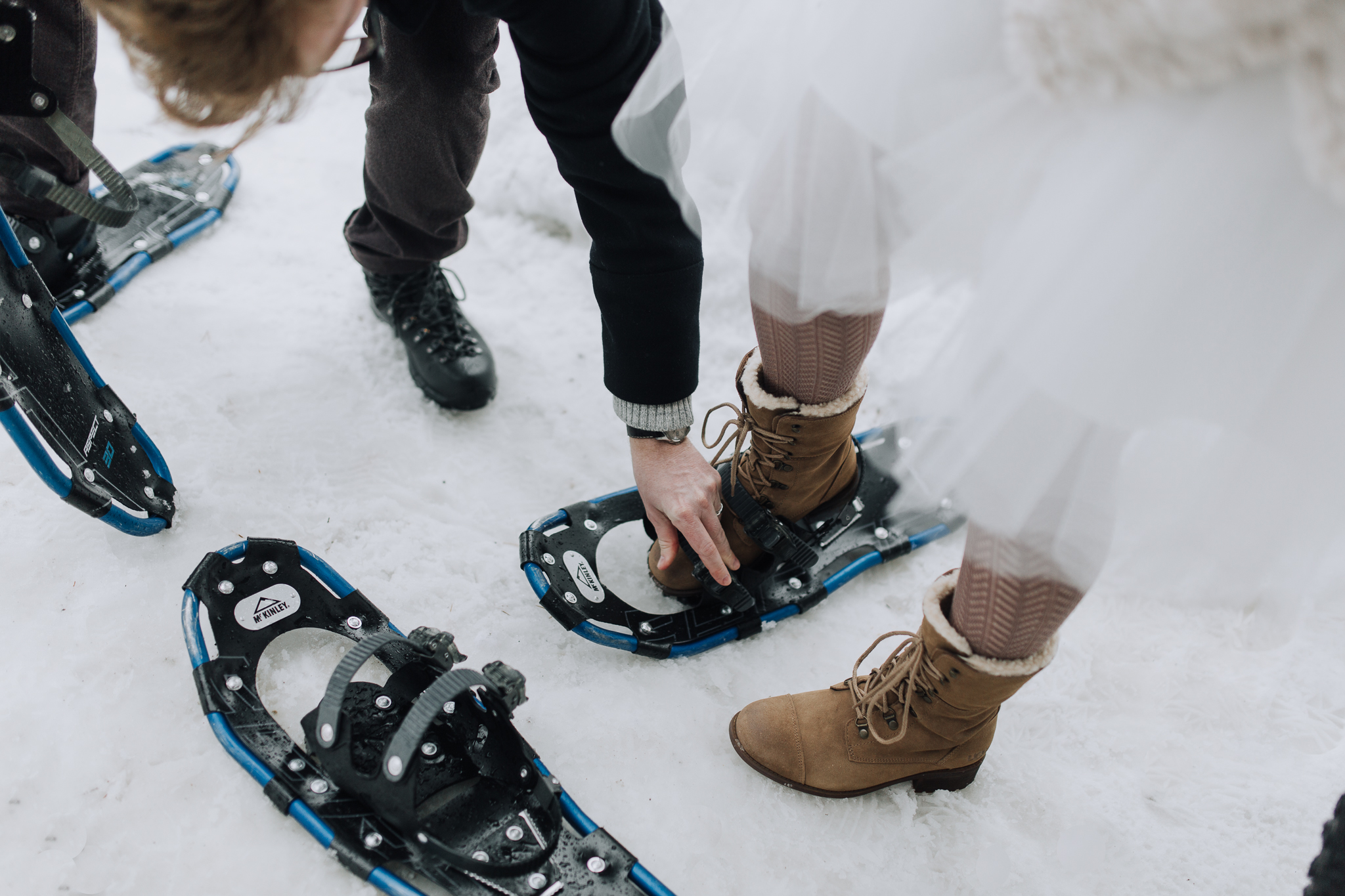 Bride and groom putting on snowshoes after intimate wedding in Banff National Park