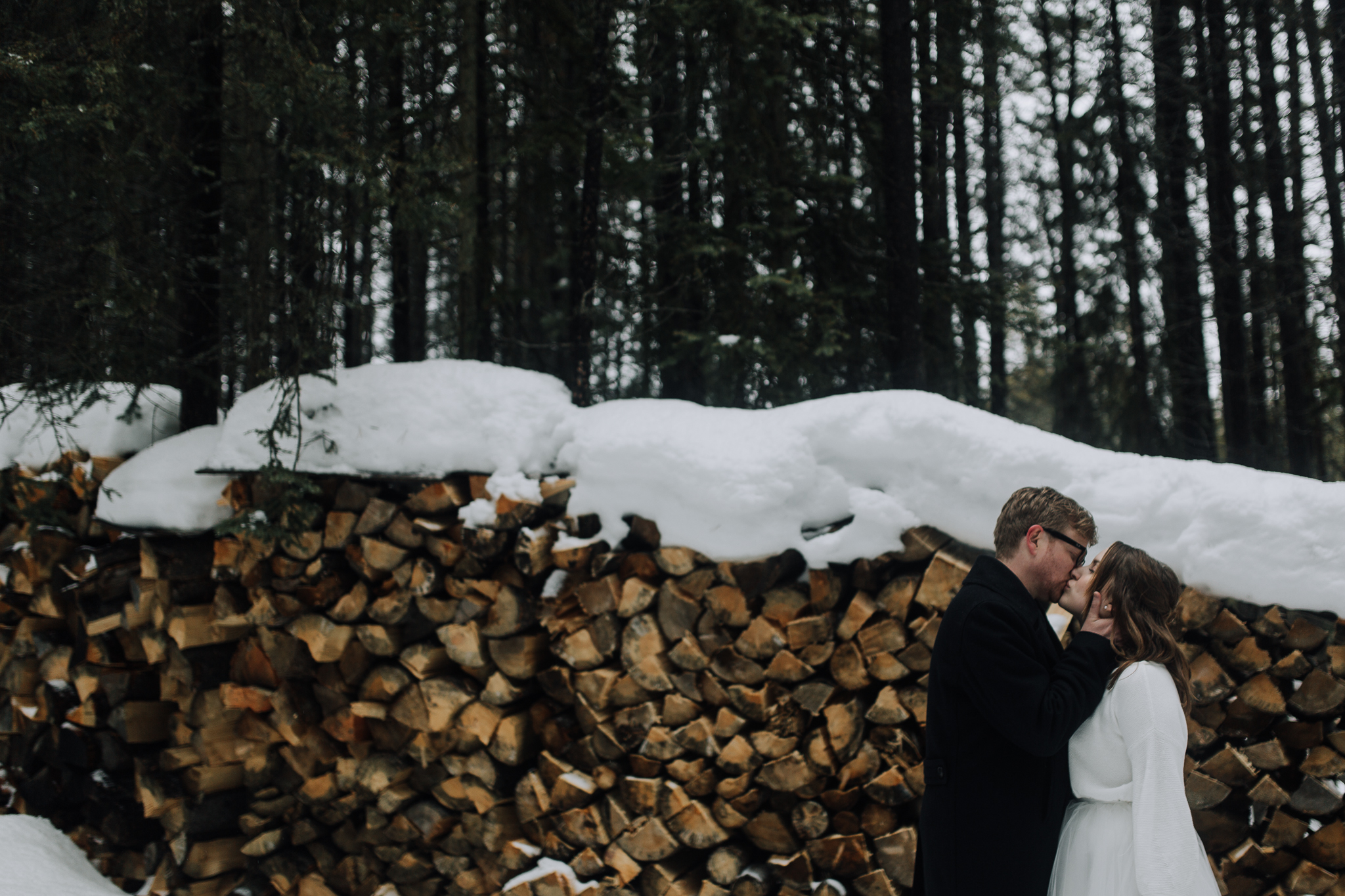 Bride and groom kissing by woodpile at Emerald Lake Lodge