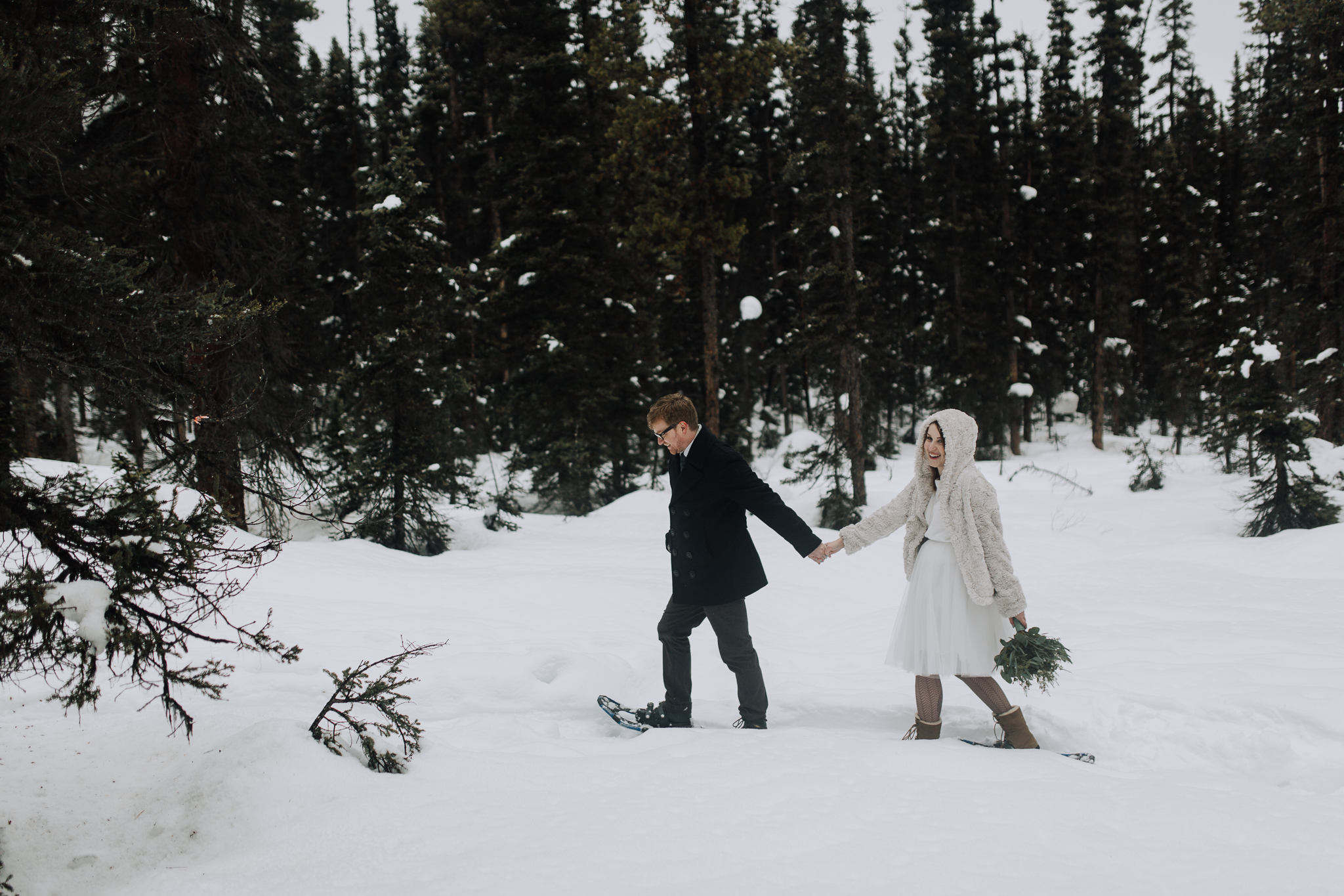 Bride and groom snowshoeing through trees holding hands at Storm Mountain Lodge