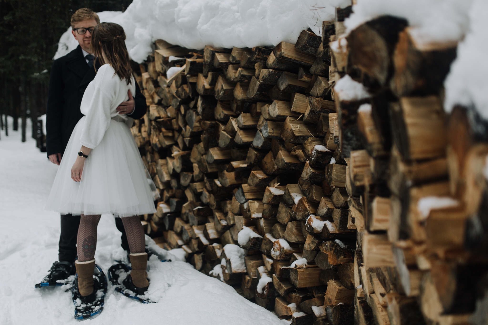 Bride and groom standing by woodpile at Emerald Lake Lodge
