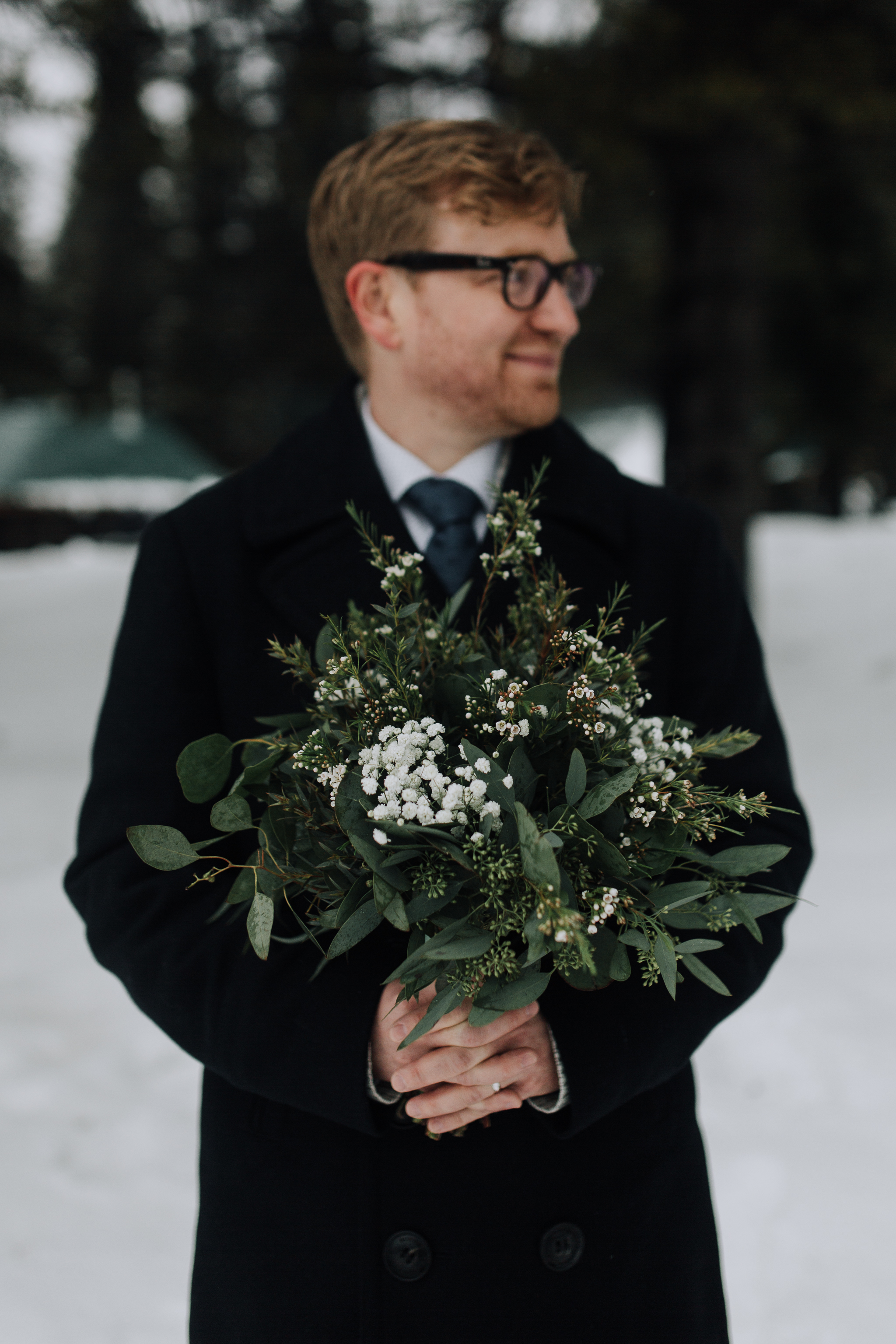 Groom holding bouquet of green florals in snow after elopement at Emerald Lake Lodge