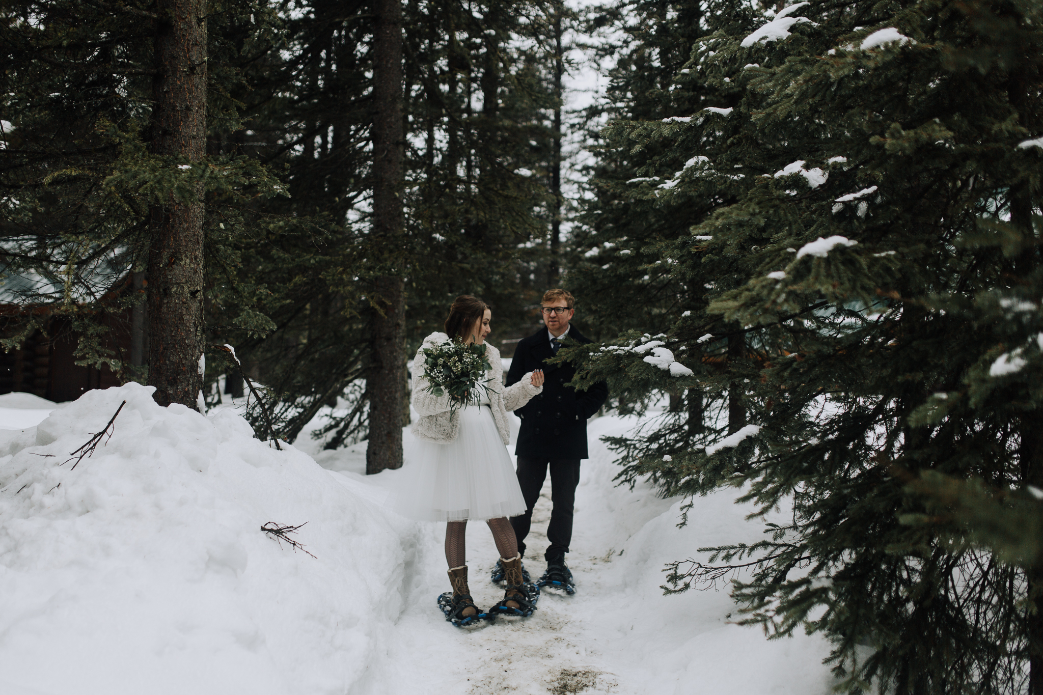 Bride and groom standing among snow covered trees at Emerald Lake Lodge