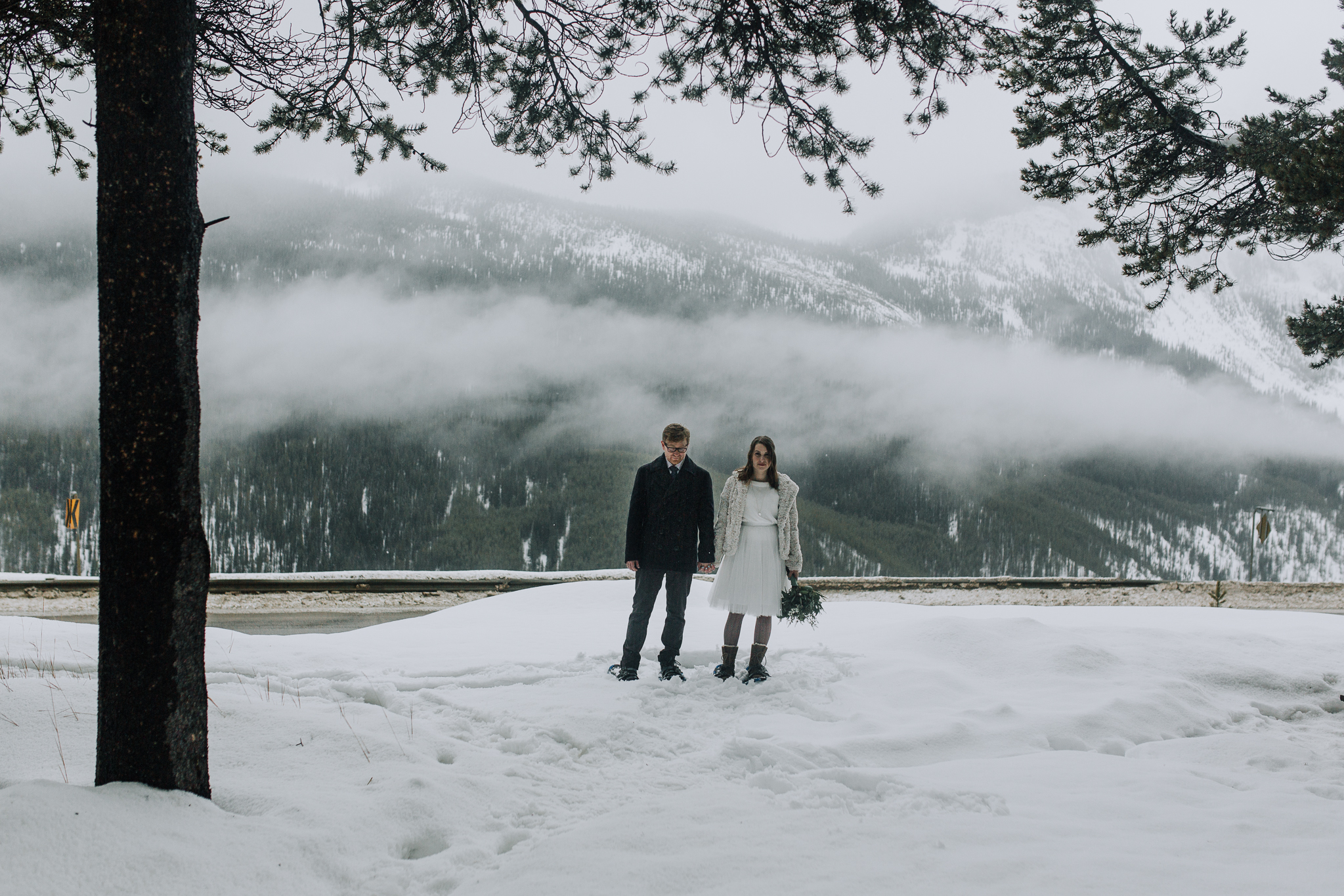 Bride and groom holding hands with misty mountains of Banff in the background