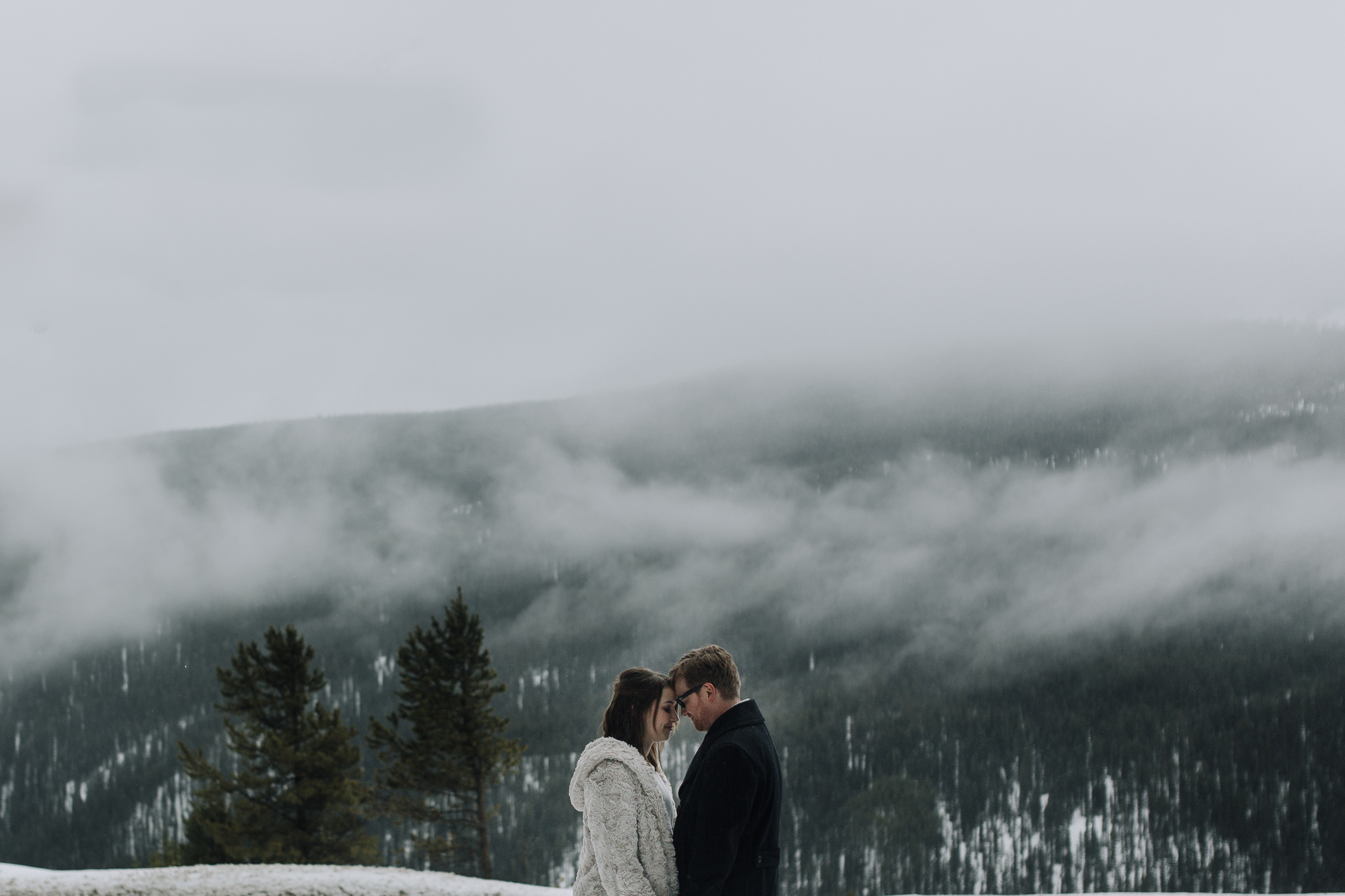 Bride and groom facing each other with foggy mountain in the background after intimate winter wedding