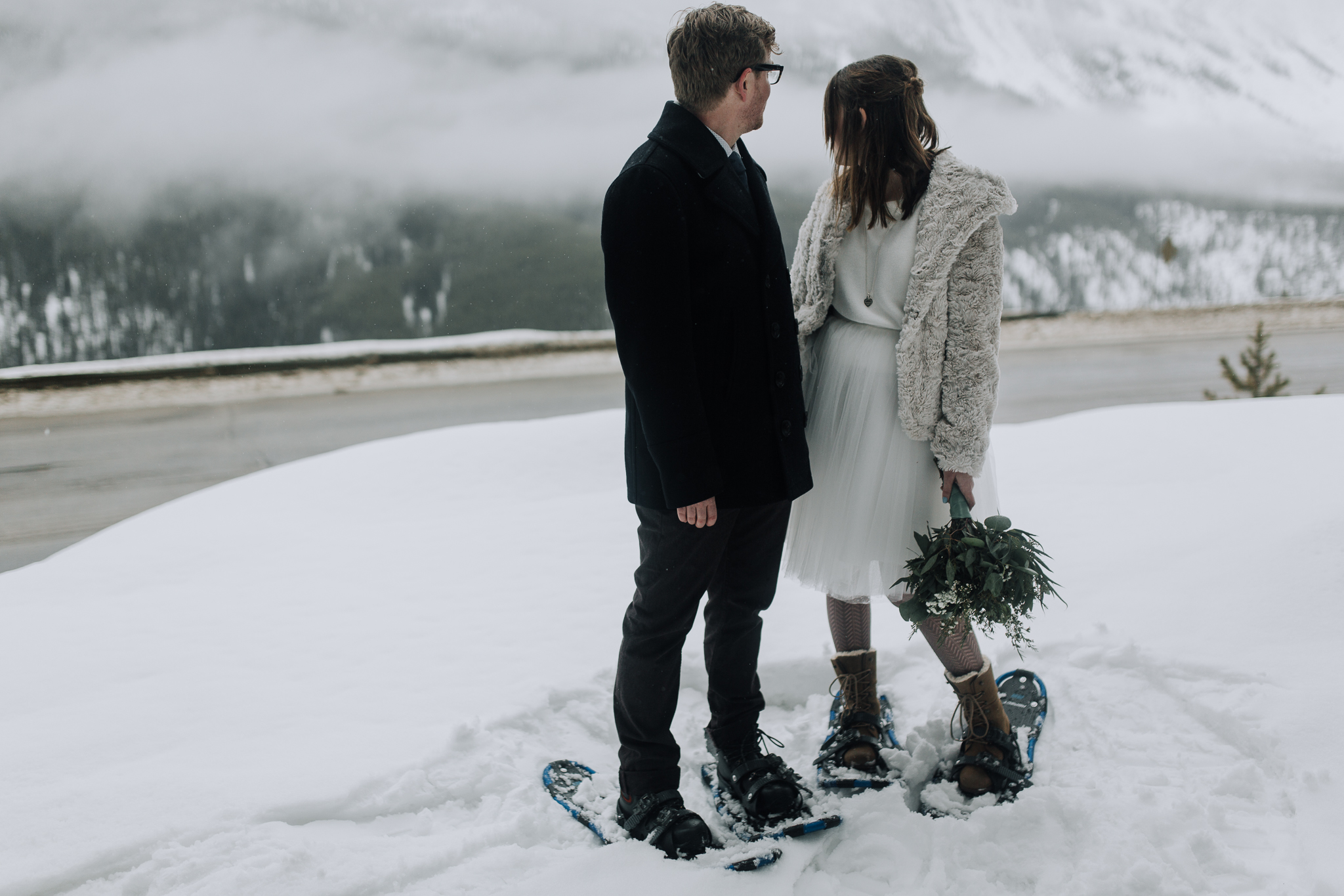 Bride and groom looking at foggy mountains in Banff National Park