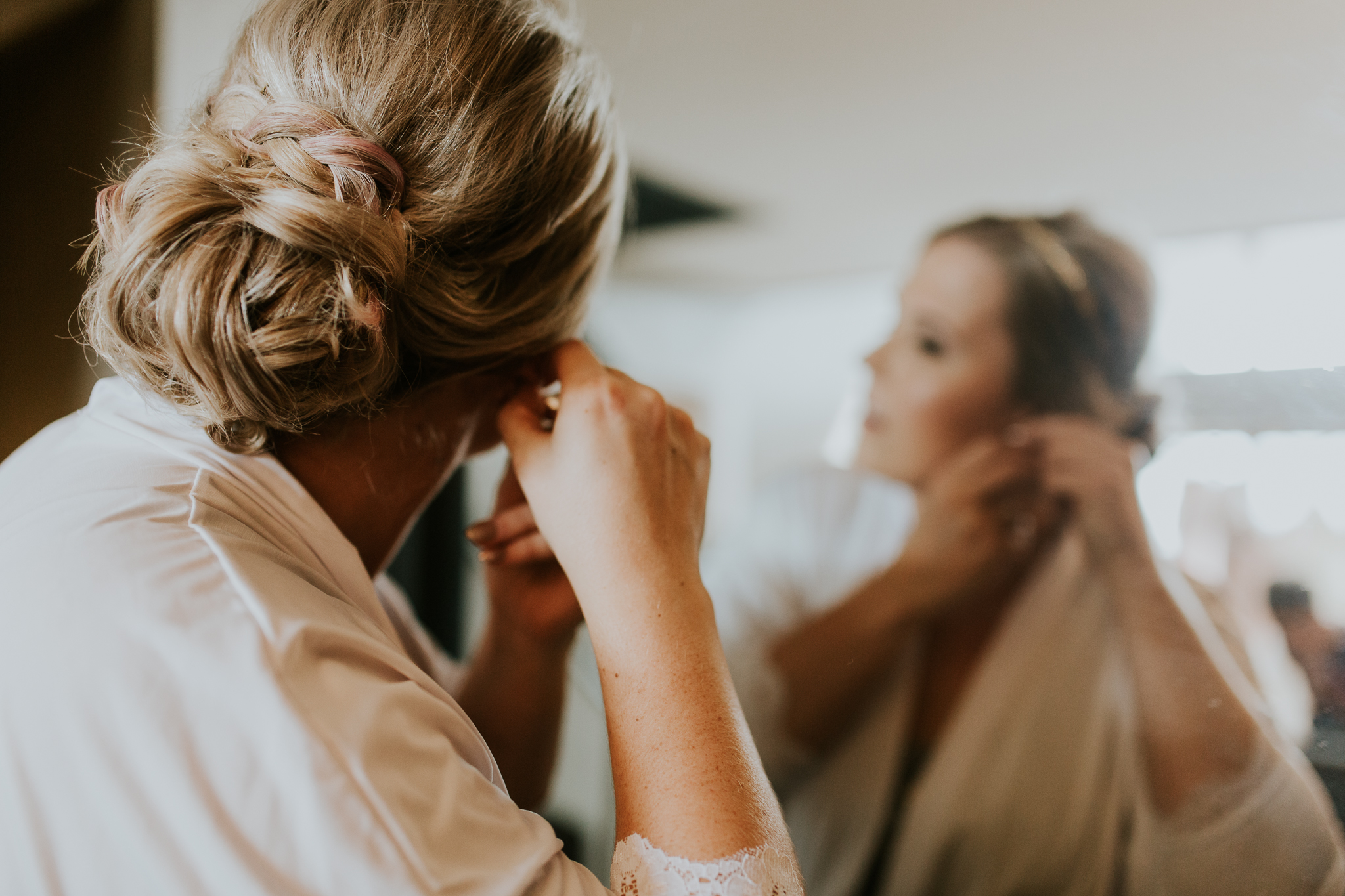 Bride putting on earrings in mirror in Kananaskis