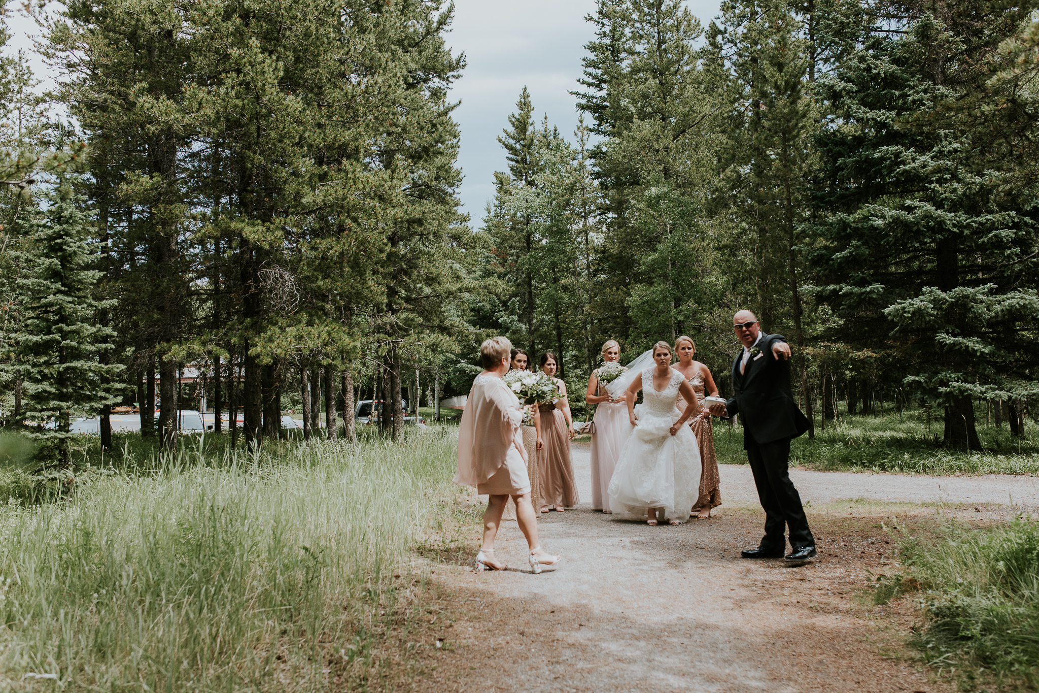 Bridal party walking through forest path to ceremony site at Delta Kananaskis