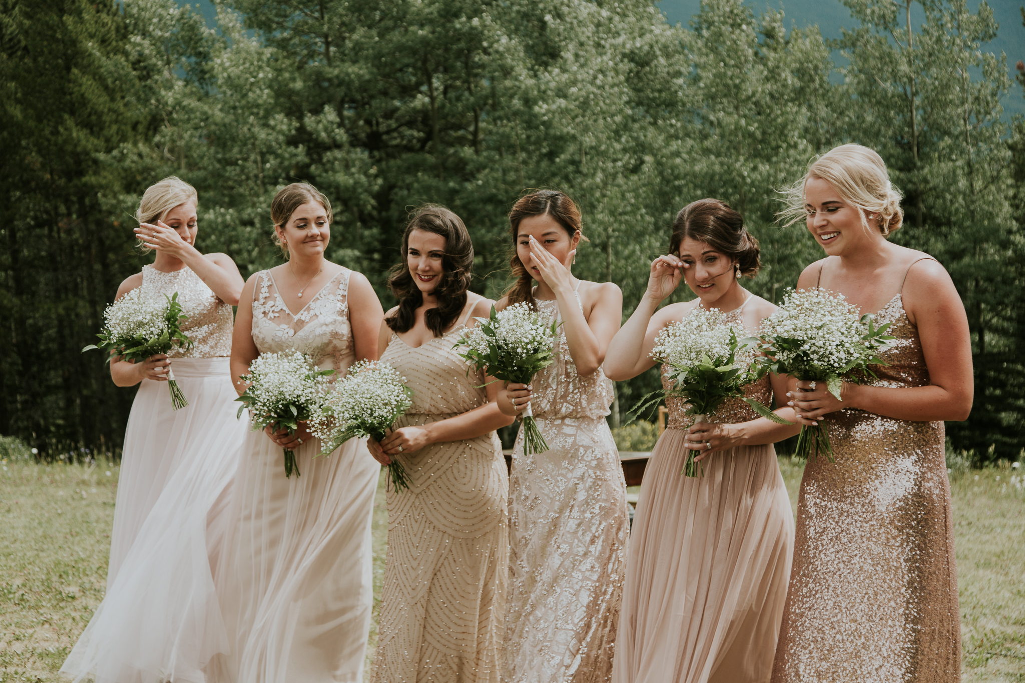 Bridesmaids wiping tears away during emotional weddingat Delta Kananaskis
