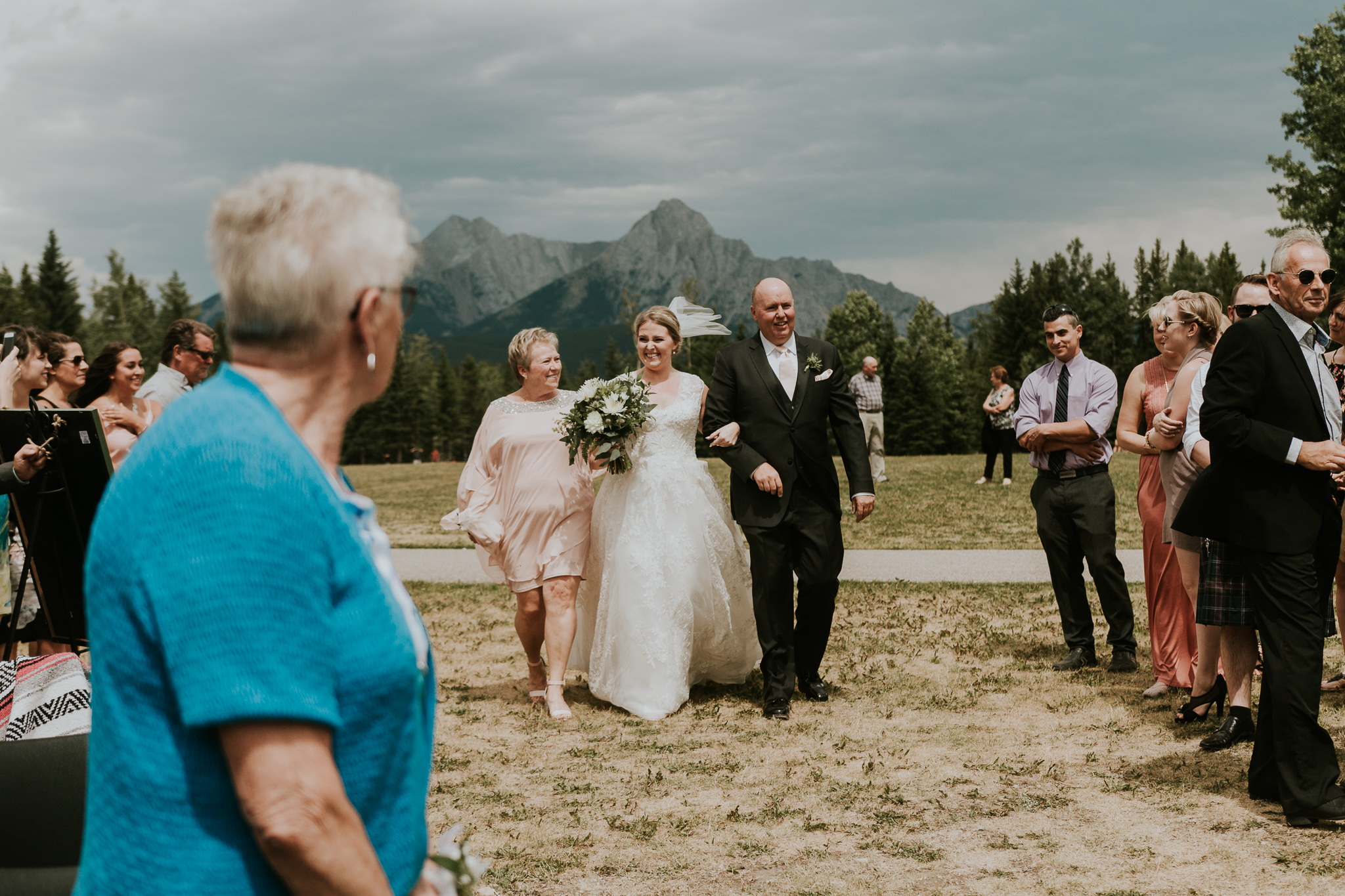 Bride walking down aisle with parents at Delta Kananaskis wedding