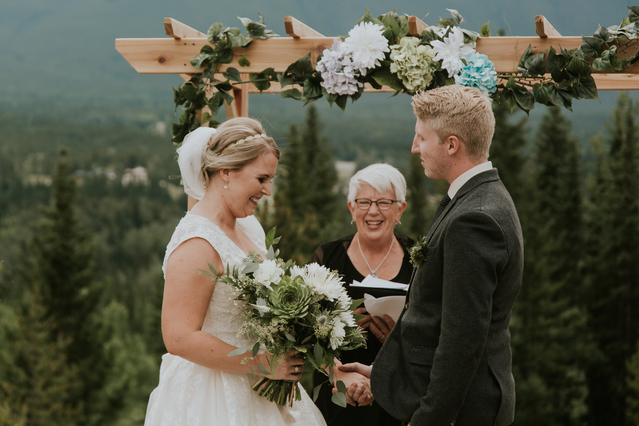 Bride and groom holding hands under arch at Delta Kananaskis