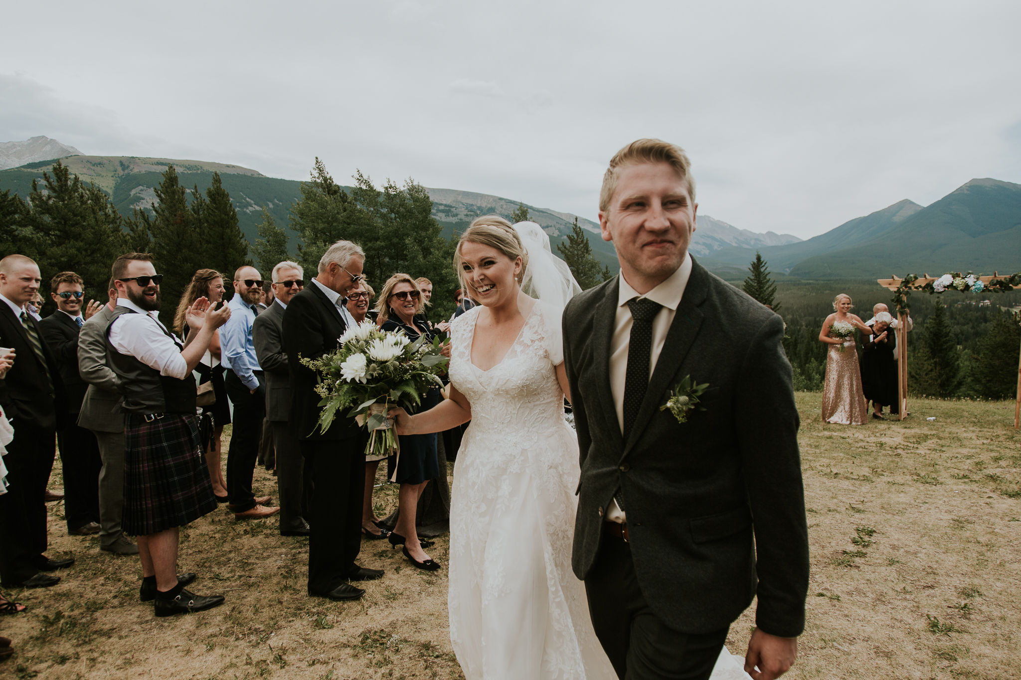 Bride and groom walk down ceremony aisle with view of mountains at Delta Kananaskis