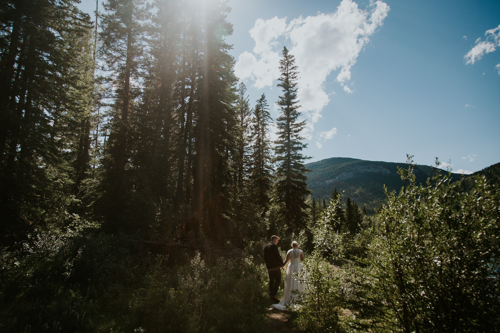 Bride and groom walking through forest at Mount Lorette Ponds at Delta Kananaskis