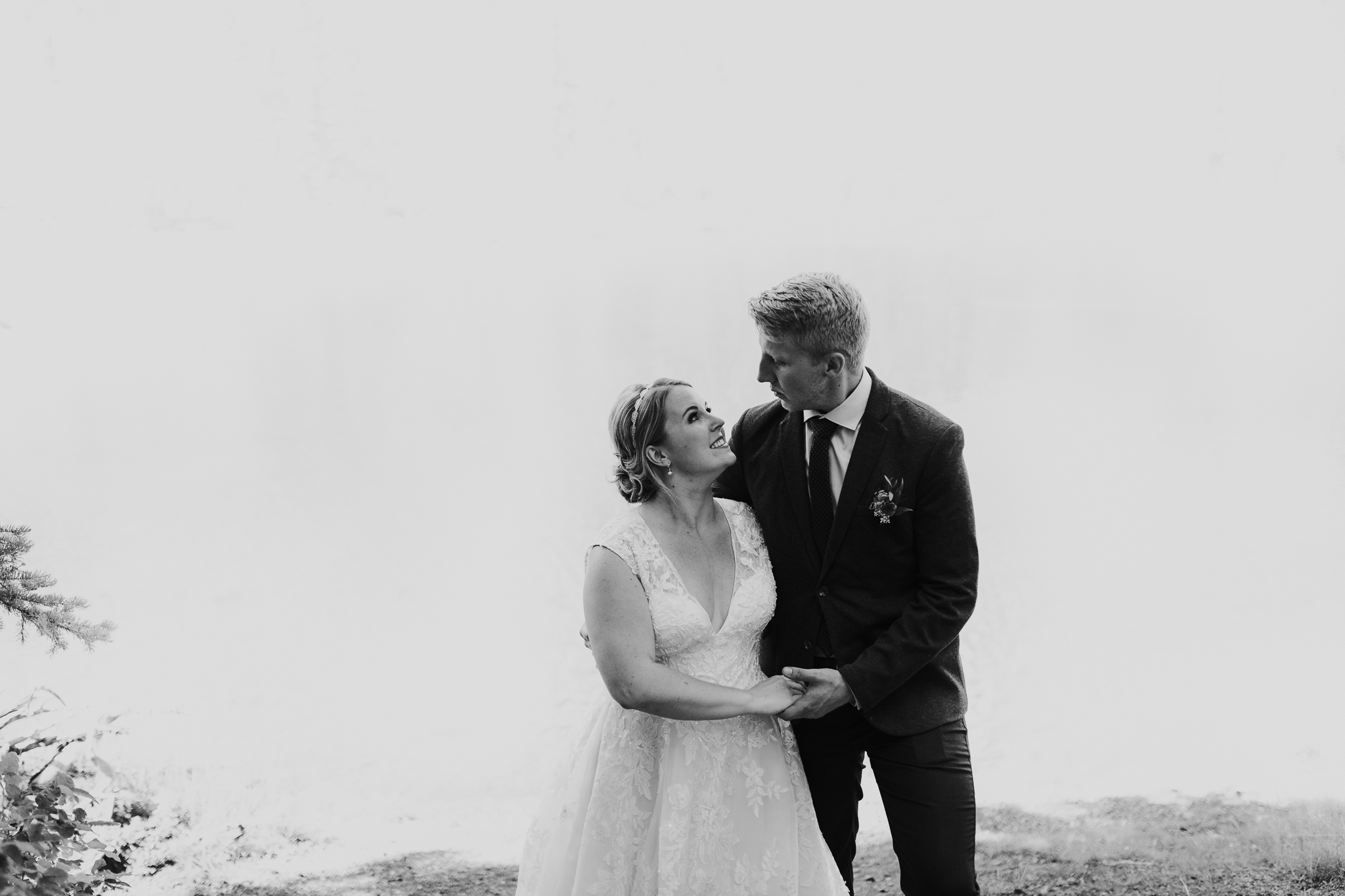 Black and white portrait of bride and groom standing at Mount Lorette ponds Kananaskis