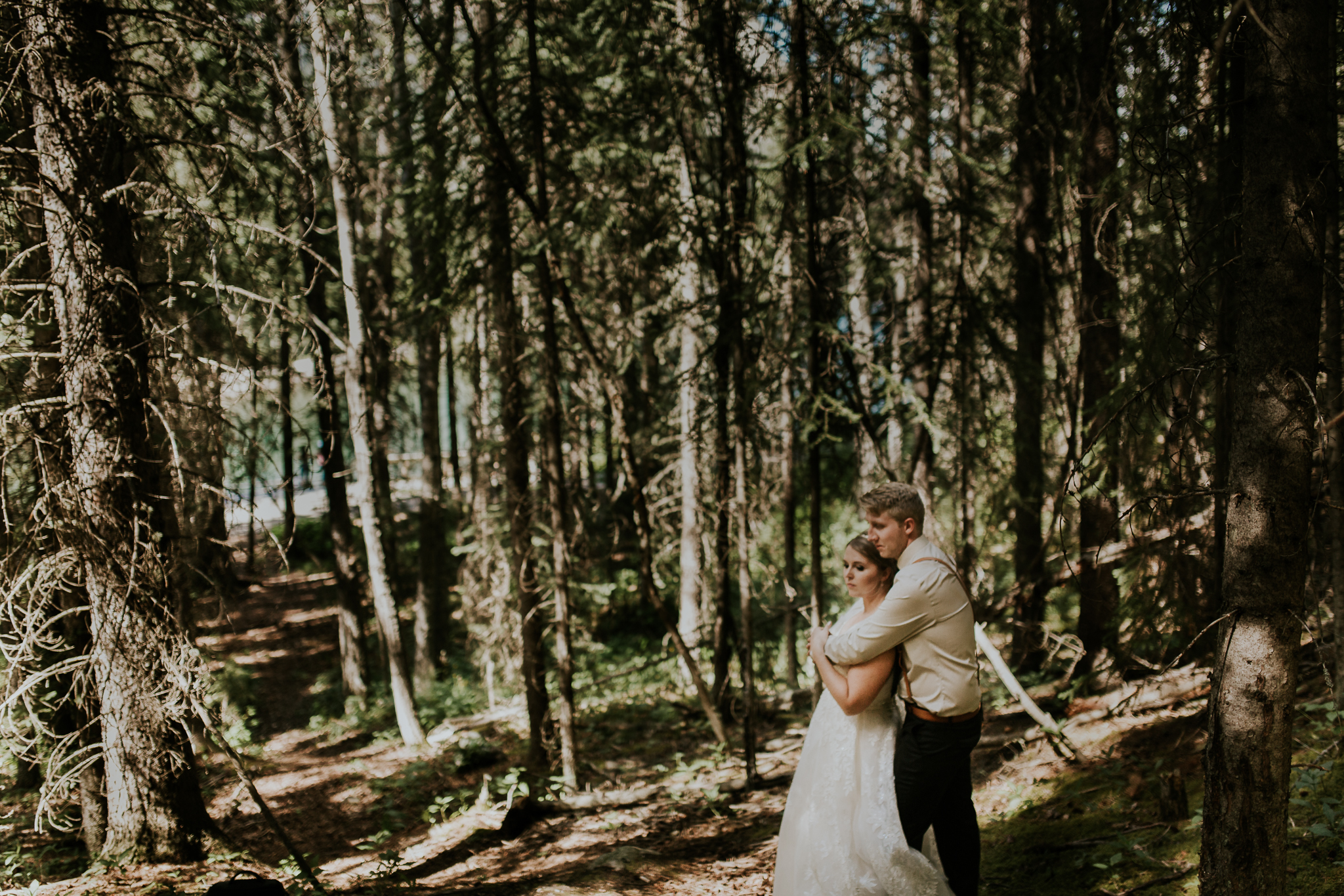 Bride and groom standing among the trees at Delta Kananaskis