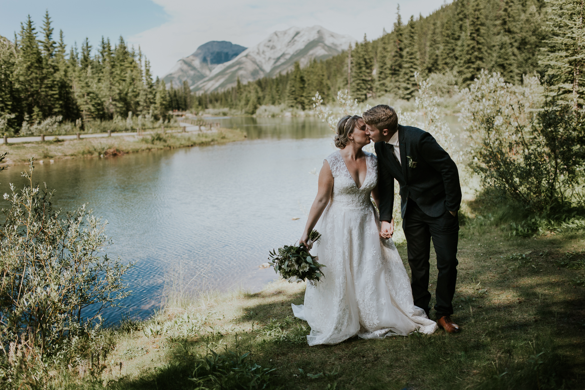 Bride and groom dancing at shore of Mount Lorette ponds Kananaskis
