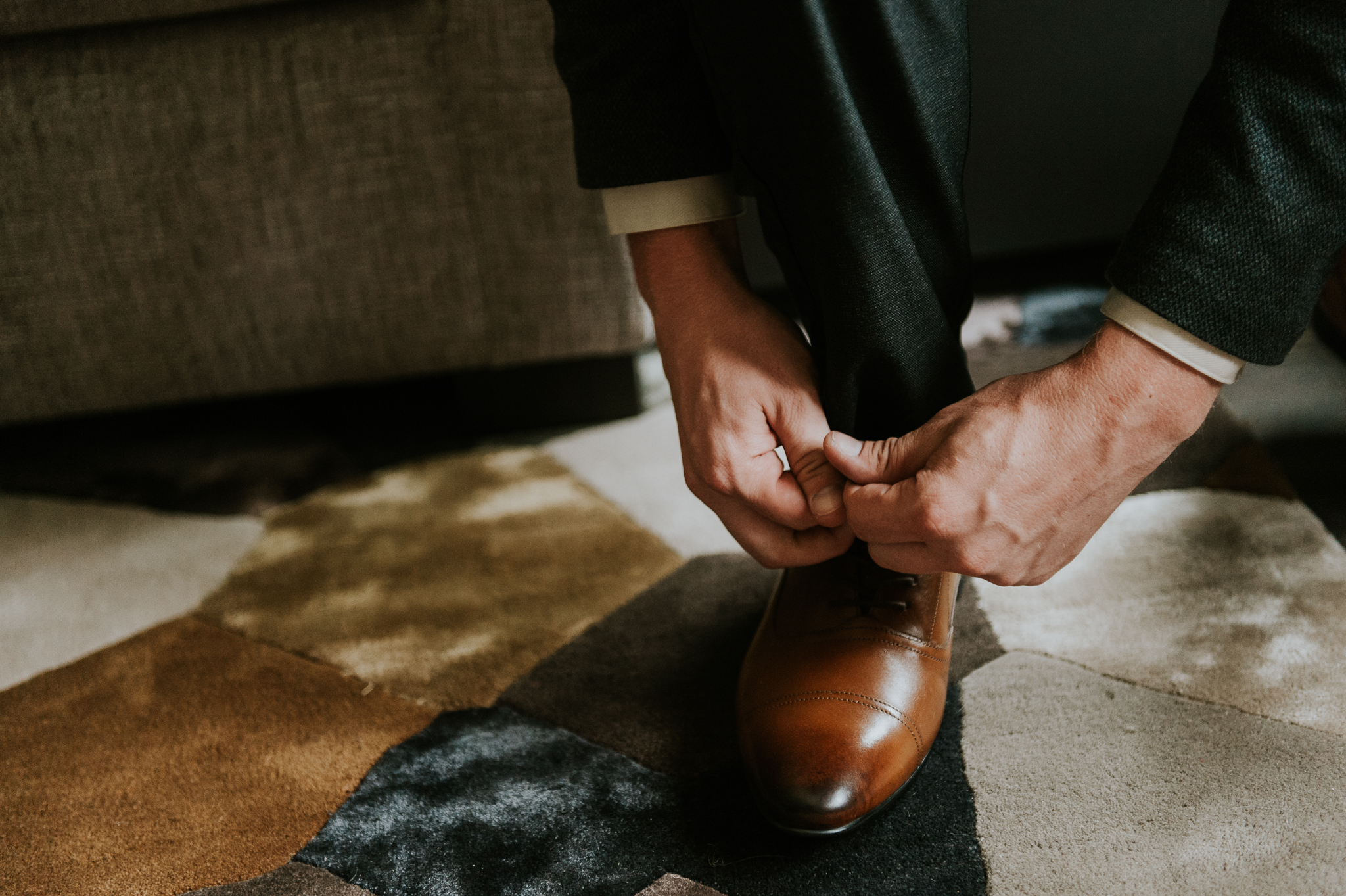 Close up of groom doing up his shoes at Delta Kananaskis