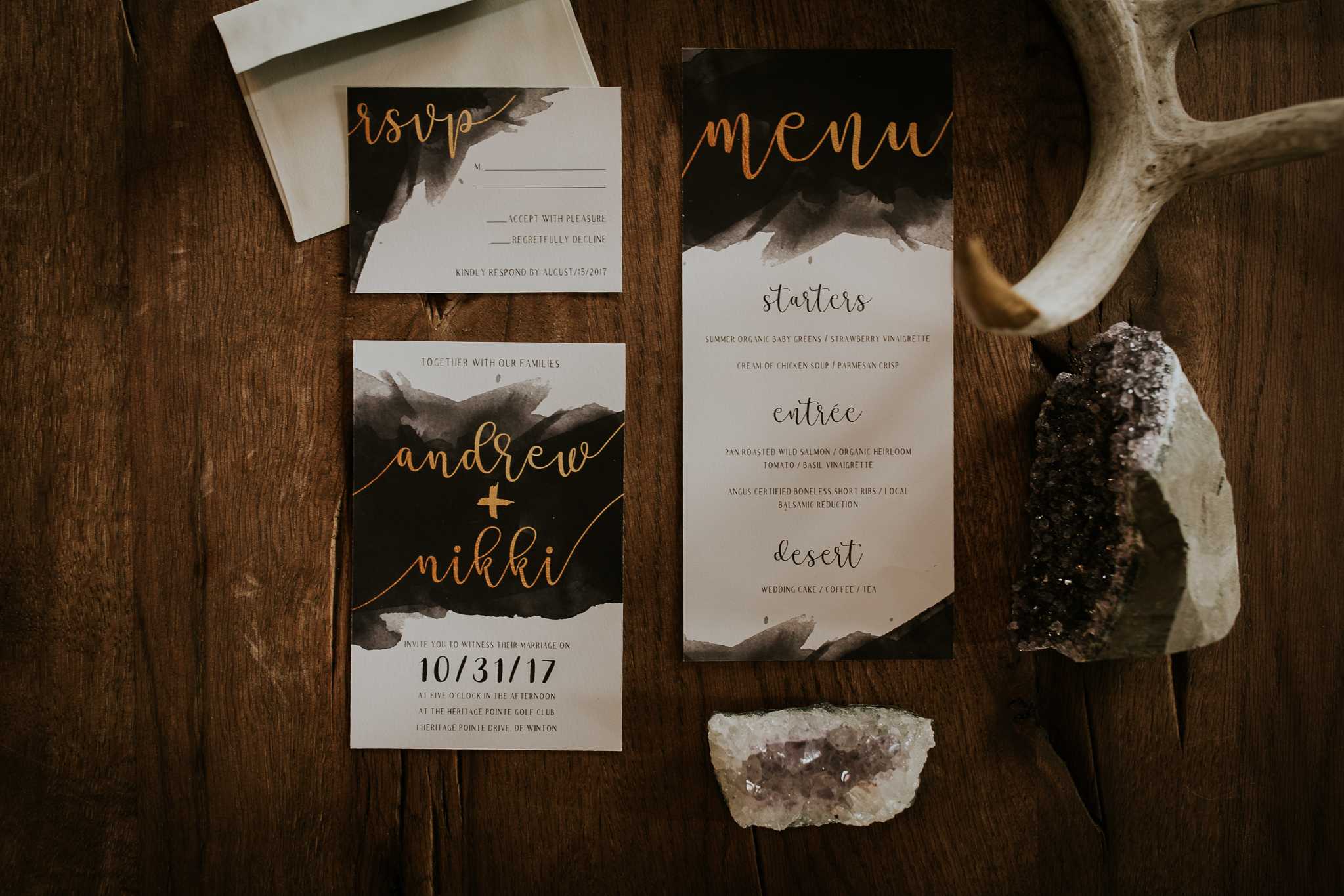 Dark and moody wedding stationary with gold font and amethyst crystal accents
