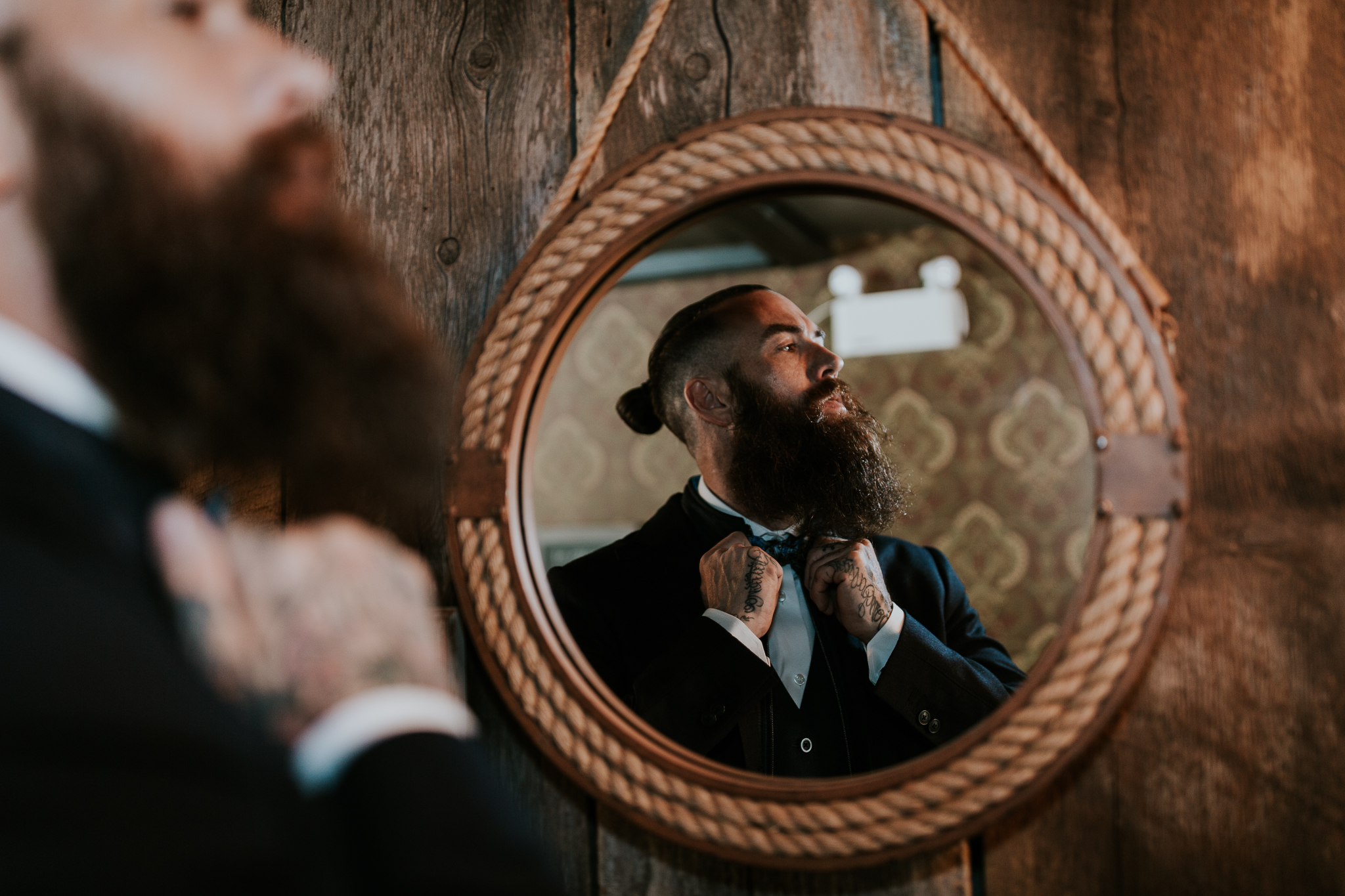 Groom fixing beard in mirror at Creekside Villa Canmore wedding