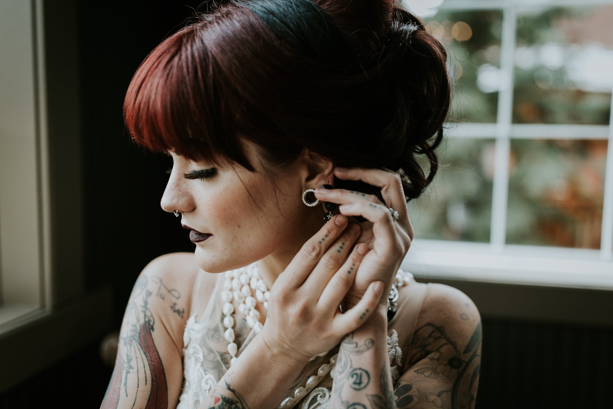 Tattooed bride with red hair adjusting earring while wearing pearls at Creekside Villag canmore