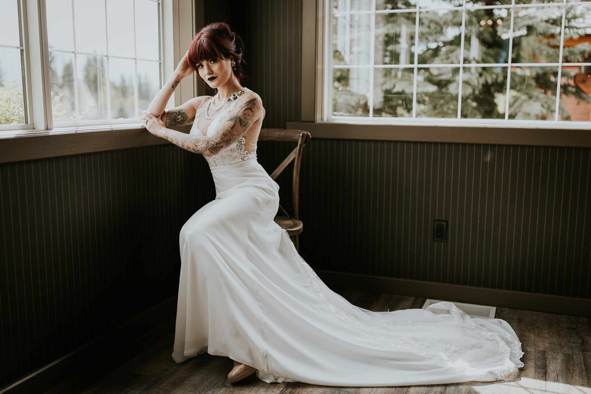 Tattooed, pin-up style bride with red hair in chair leaning against window at Creekside Villa wedding