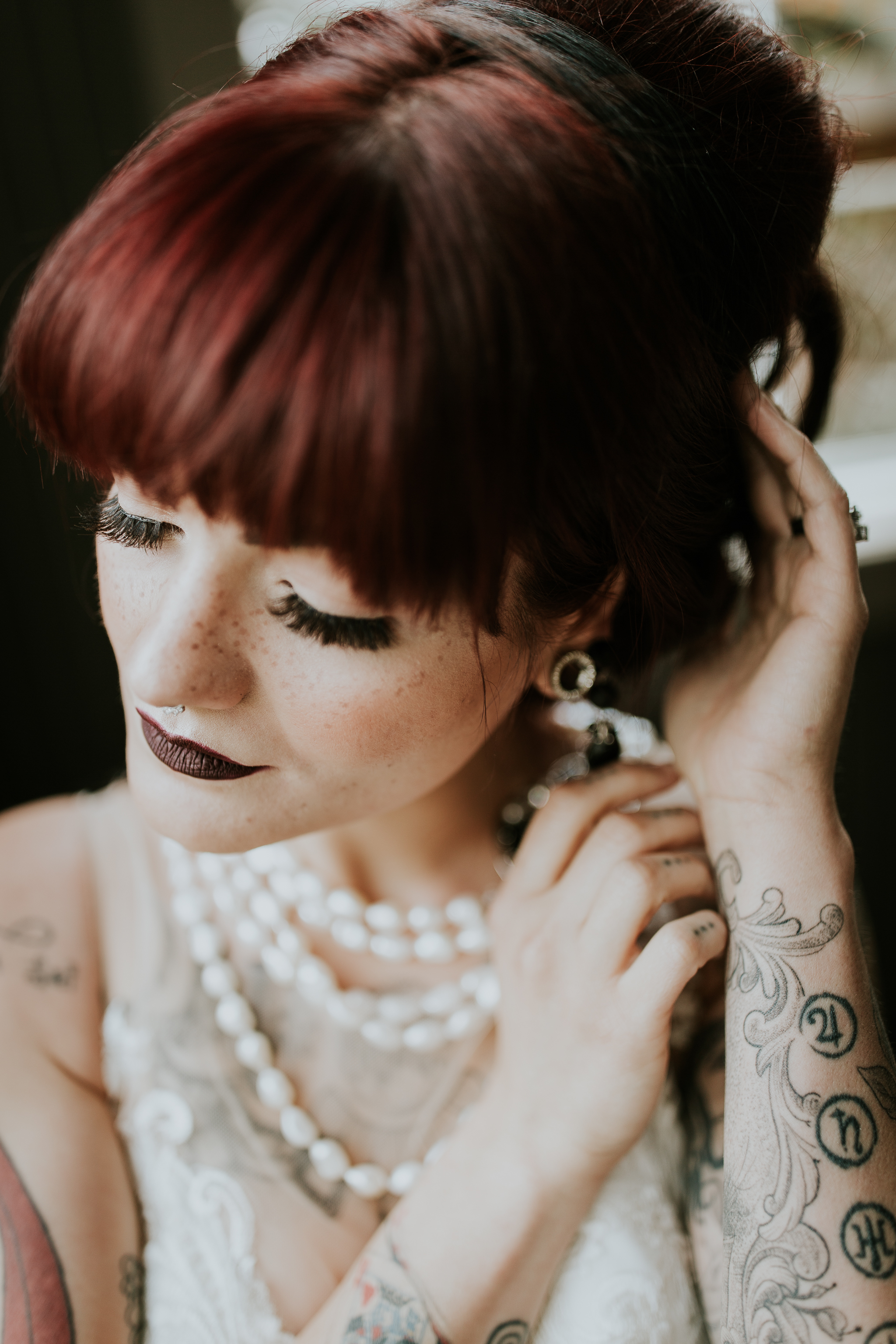 Tattooed, ginger bride adjusting hair, wearing pearls at intimate Canmore wedding