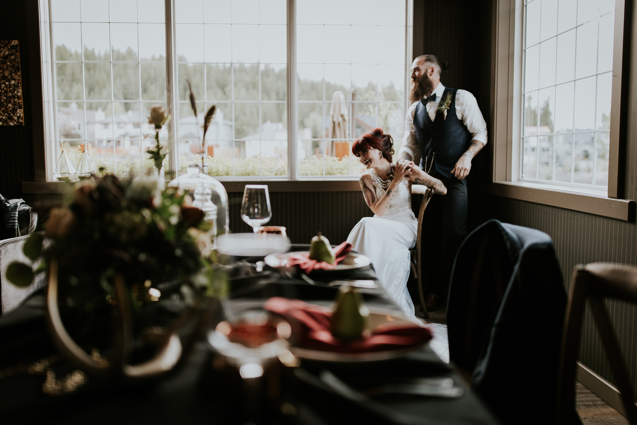 Tattooed bride and groom laughing in corner of room near sweetheart table