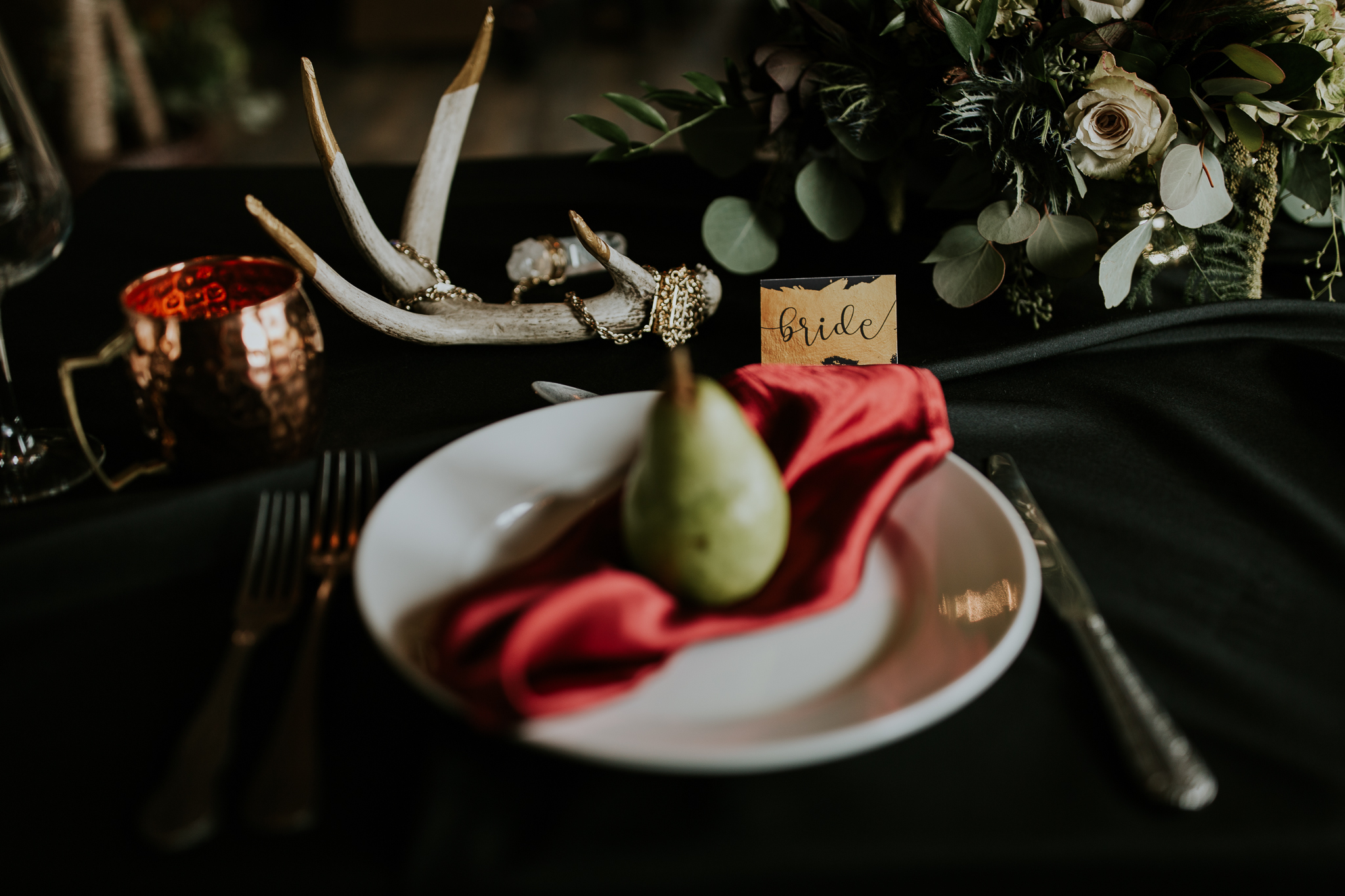 Gold, red and black colour scheme place settings for intimate wedding at Creekside Villa Canmore