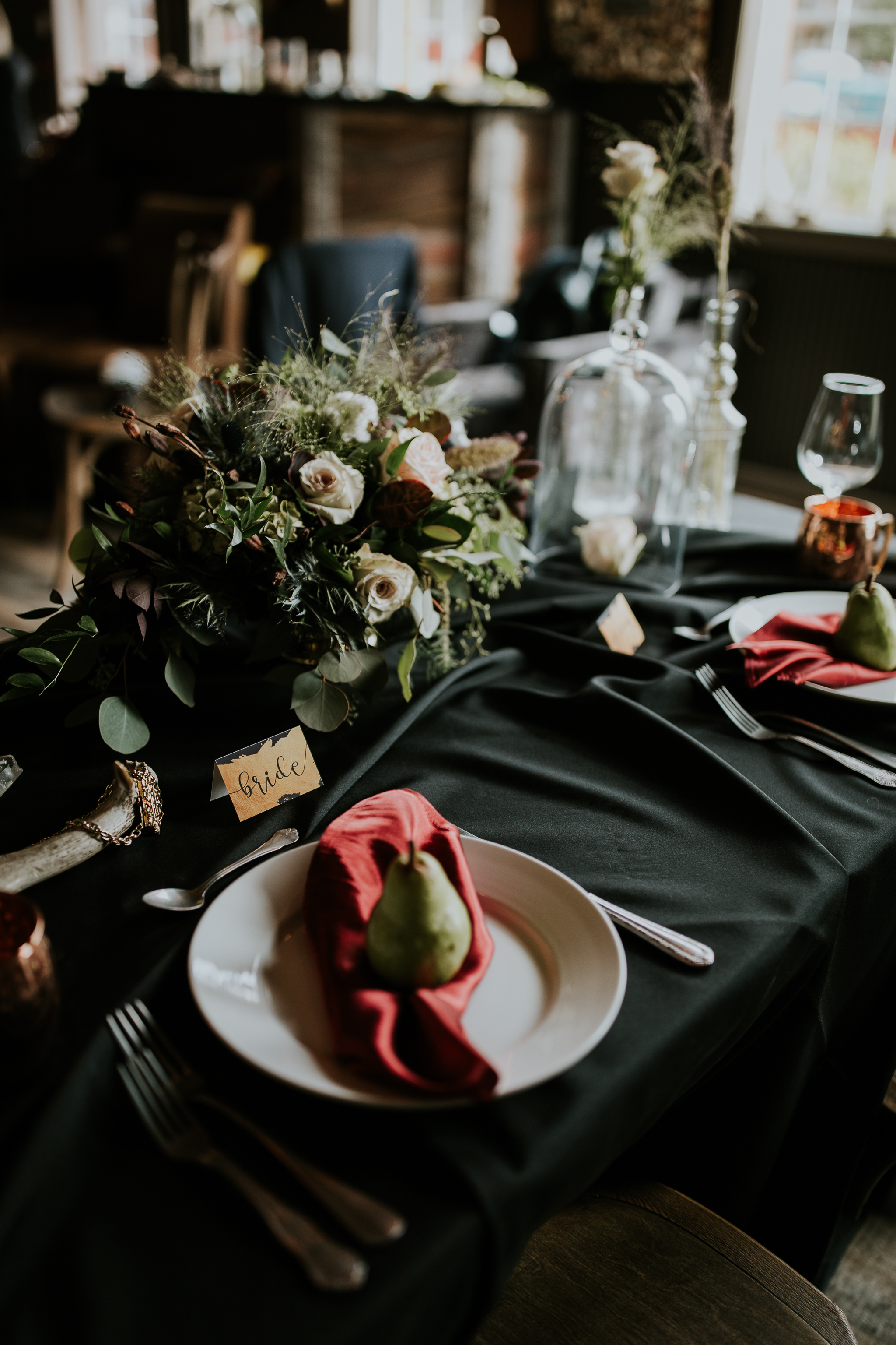 Florals and place settings for edgy creative wedding table using black, red and ggold