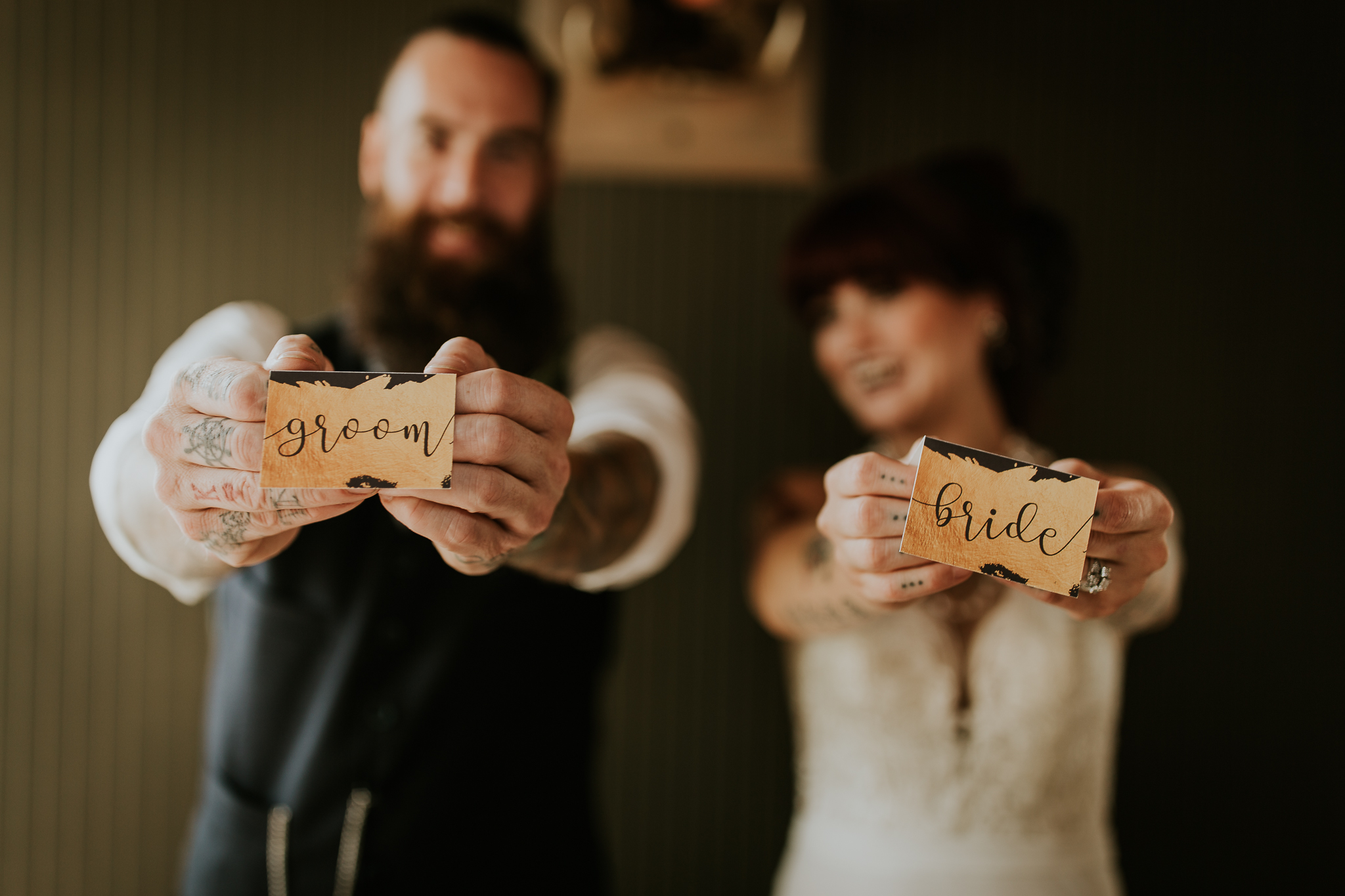 Bride and groom with tattooed hands holding out gold placeholders