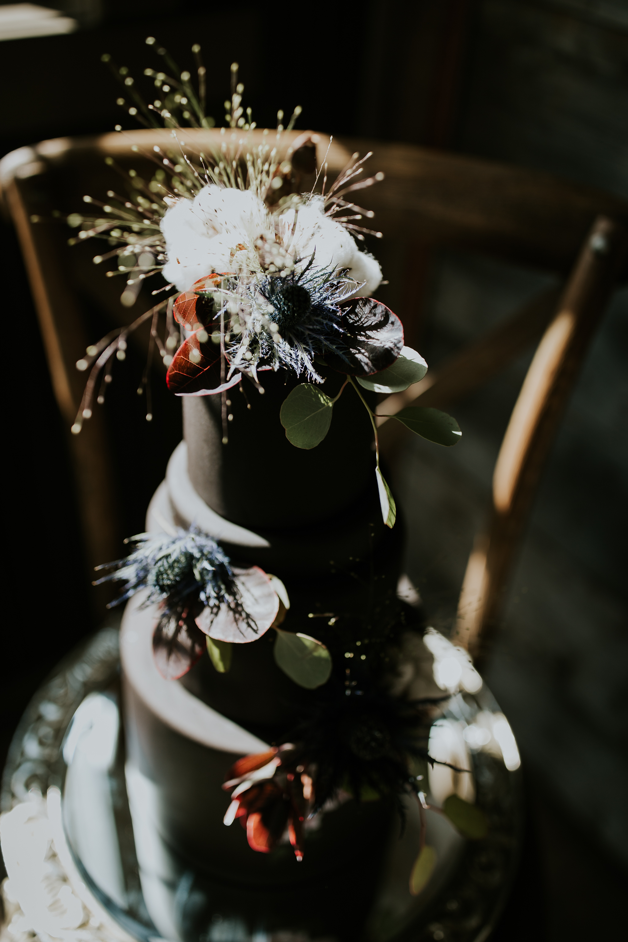 Black edgy wedding cake with feather and flower accents