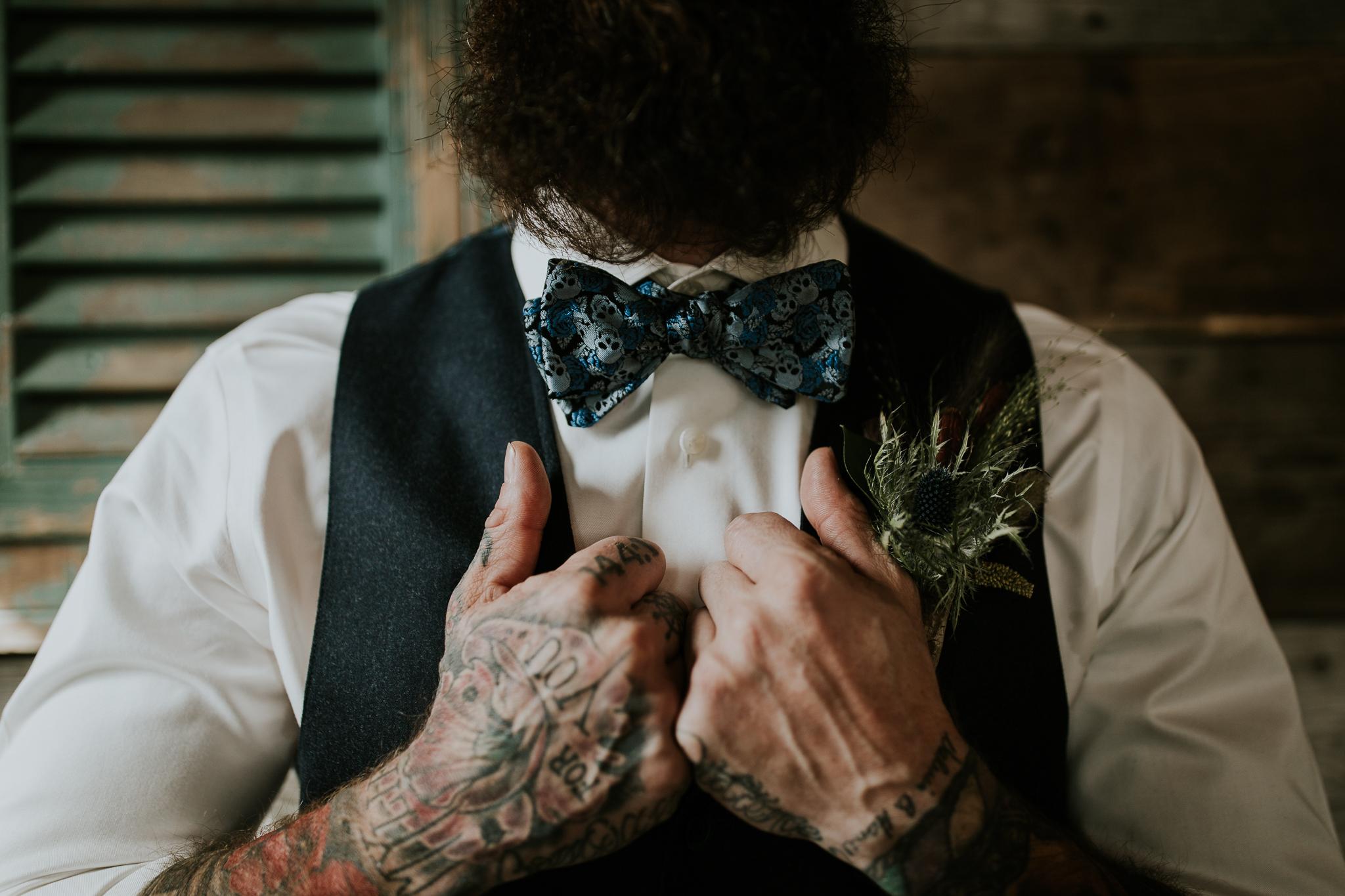 Close up of Groom's tattooed hands adjusting his wedding bowtie