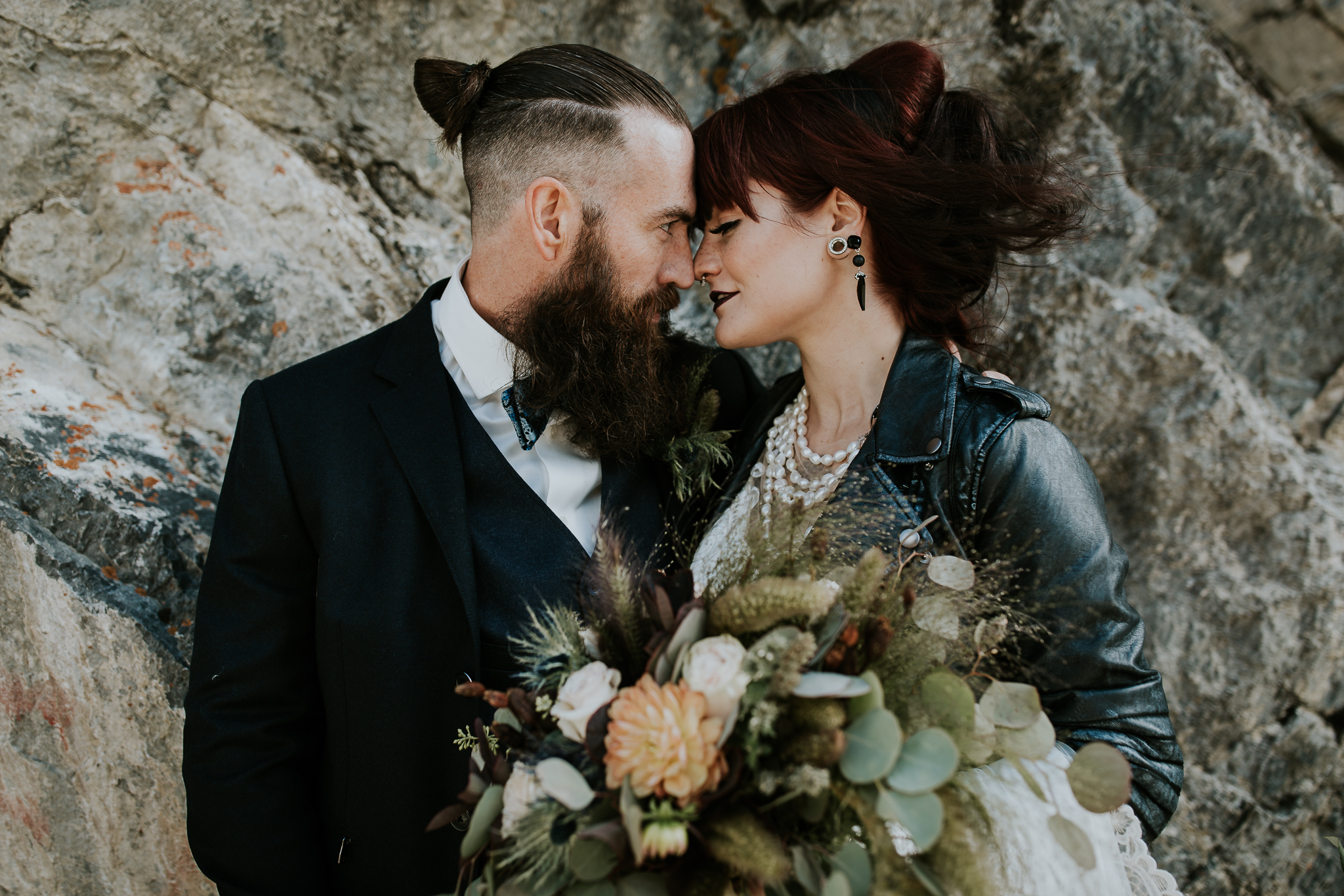 Tattooed Bride and groom looking at each other wearing leather jackets in Alberta rocky mountains
