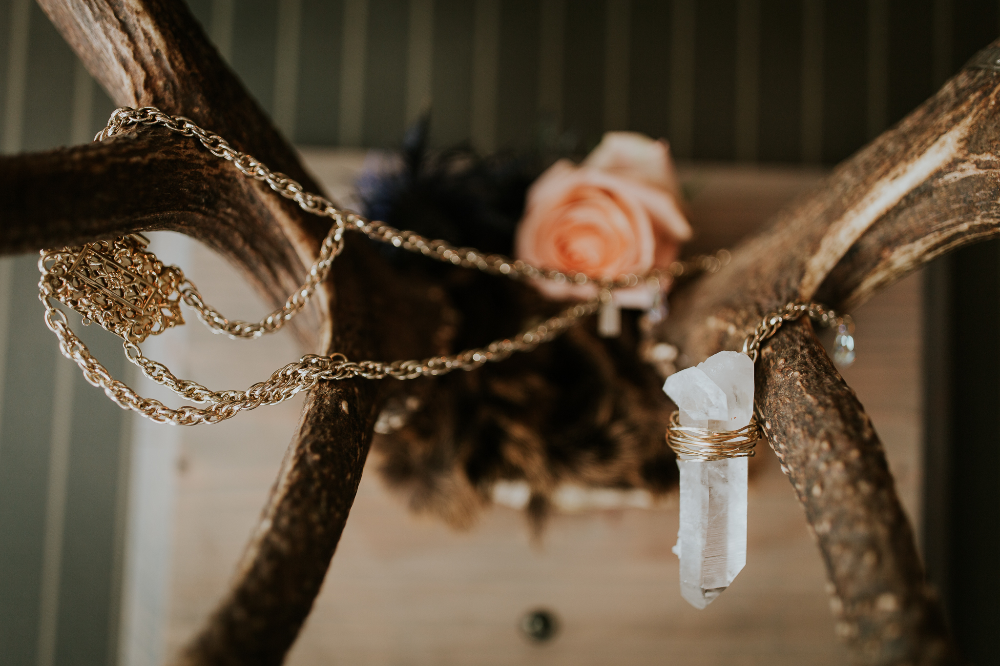 Raw quartz necklace wrapped around antler on black cloth for wedding table