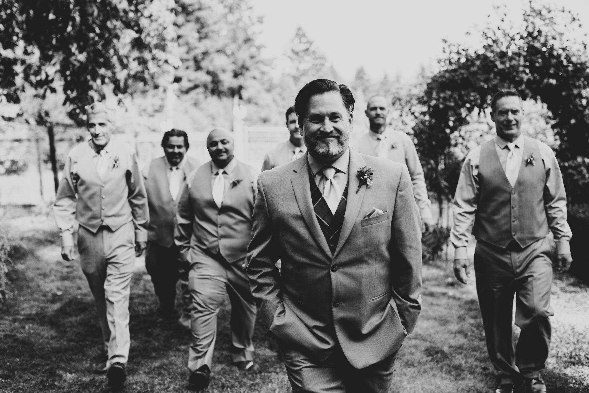 Black and white portrait of groomsmen walking toward camera at vineyard wedding on Vancouver Island