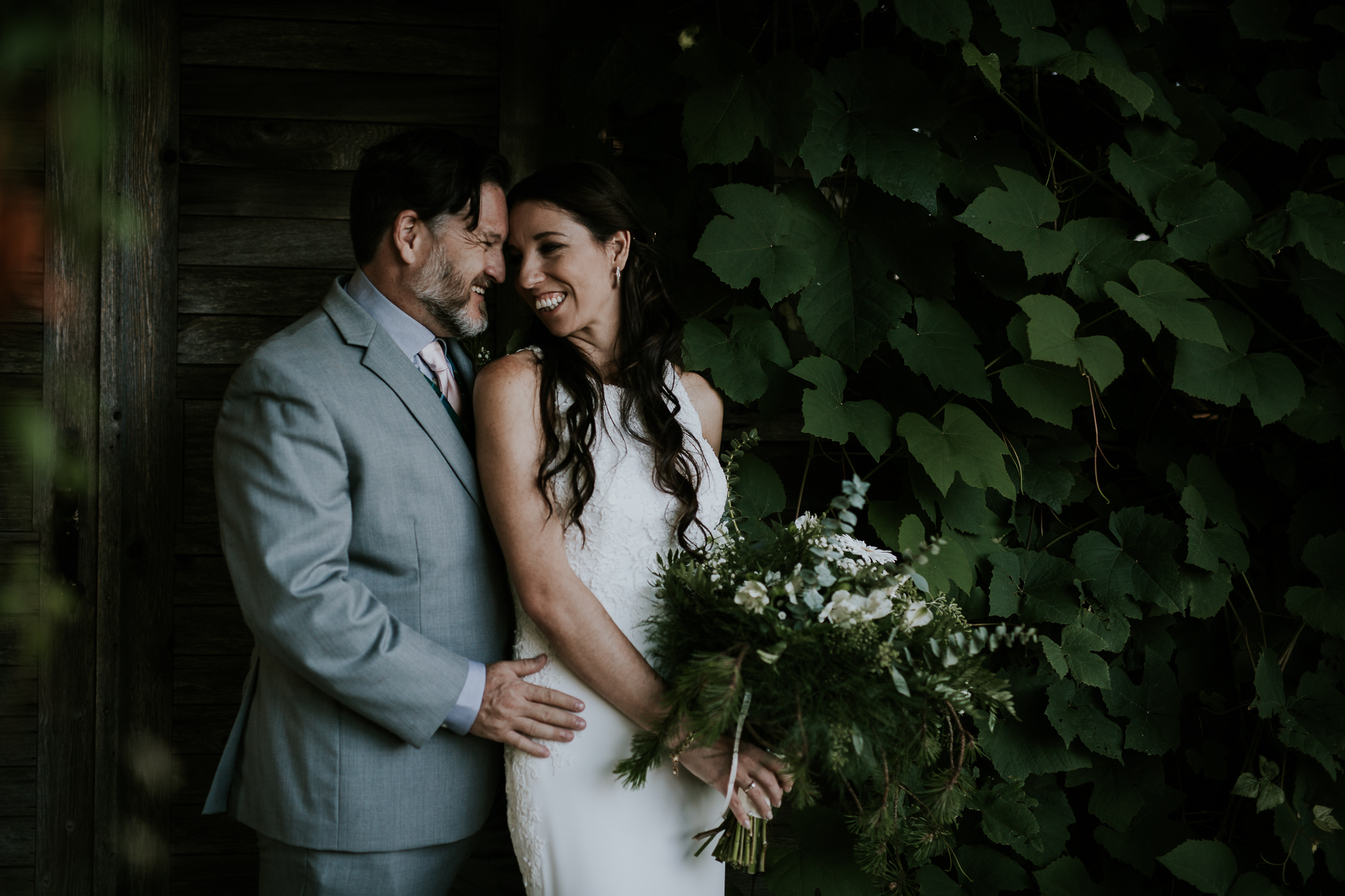 Bride and groom cuddling under climbing vines at Starling Lane winery wedding