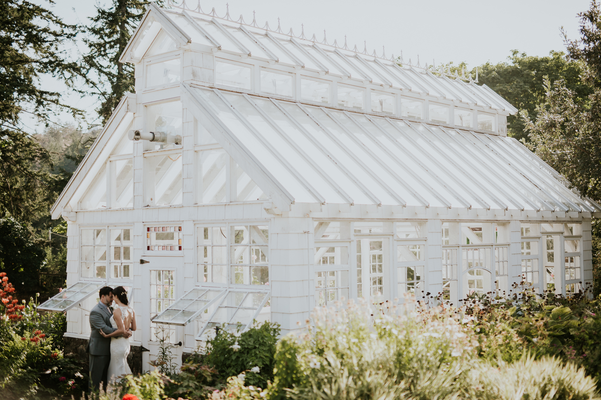 Bride and groom standing by greenhouse on Vancouver Island wedding venue