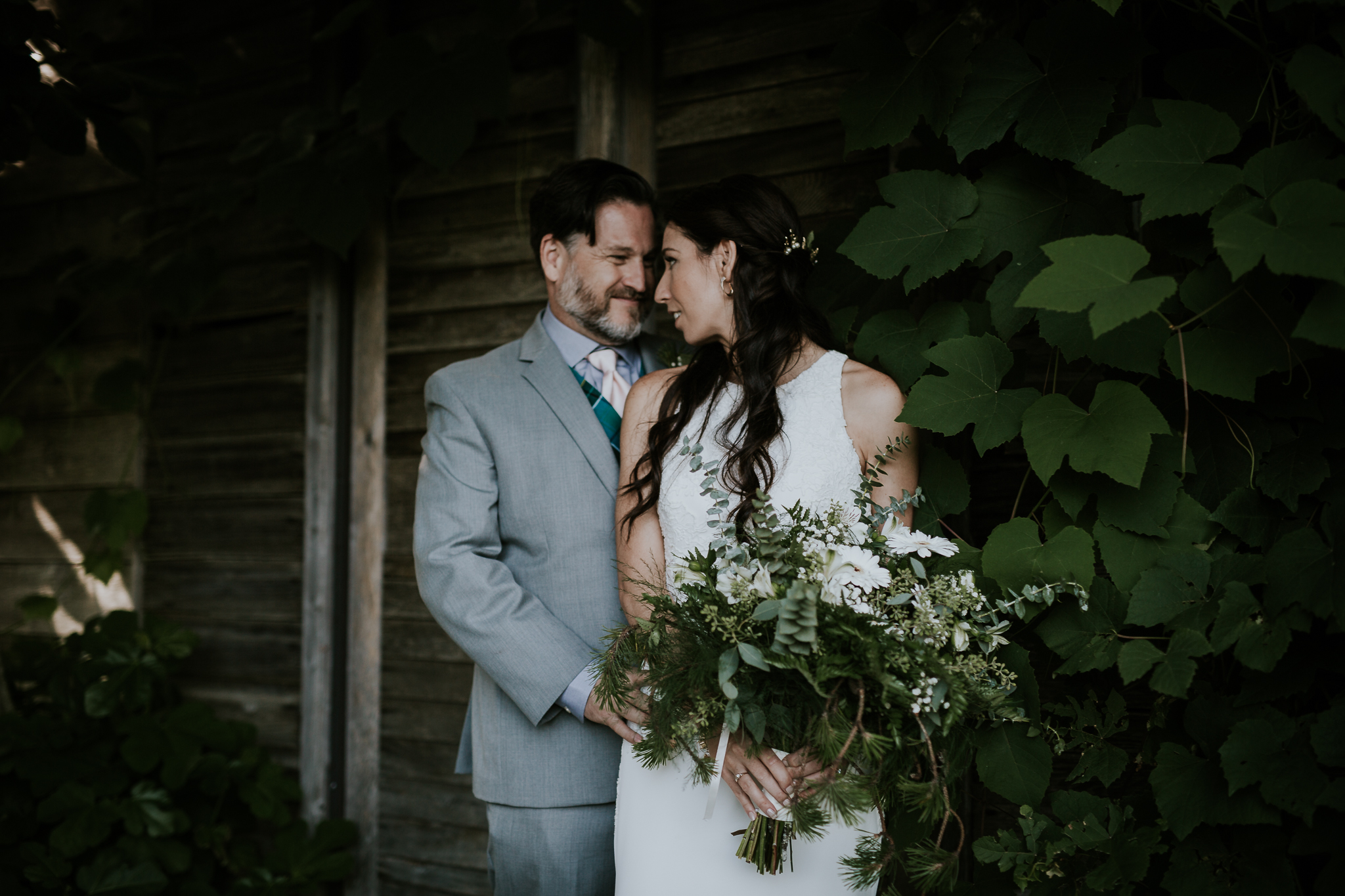 Bride and groom kissing near hydrangeas at Starling Lane winery wedding venue