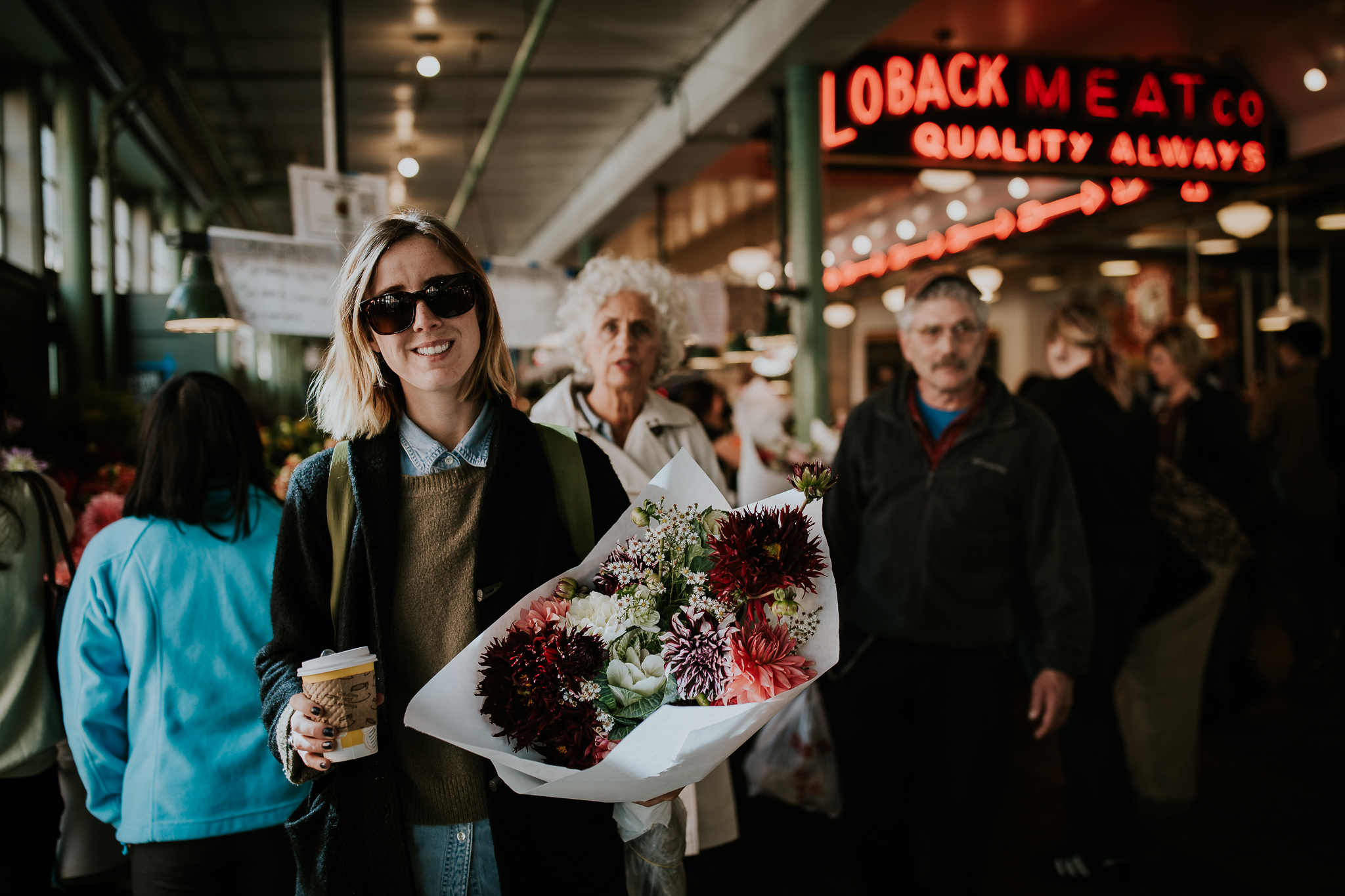 Tourist at Seattle Public Market holding coffee and bridal bouquet