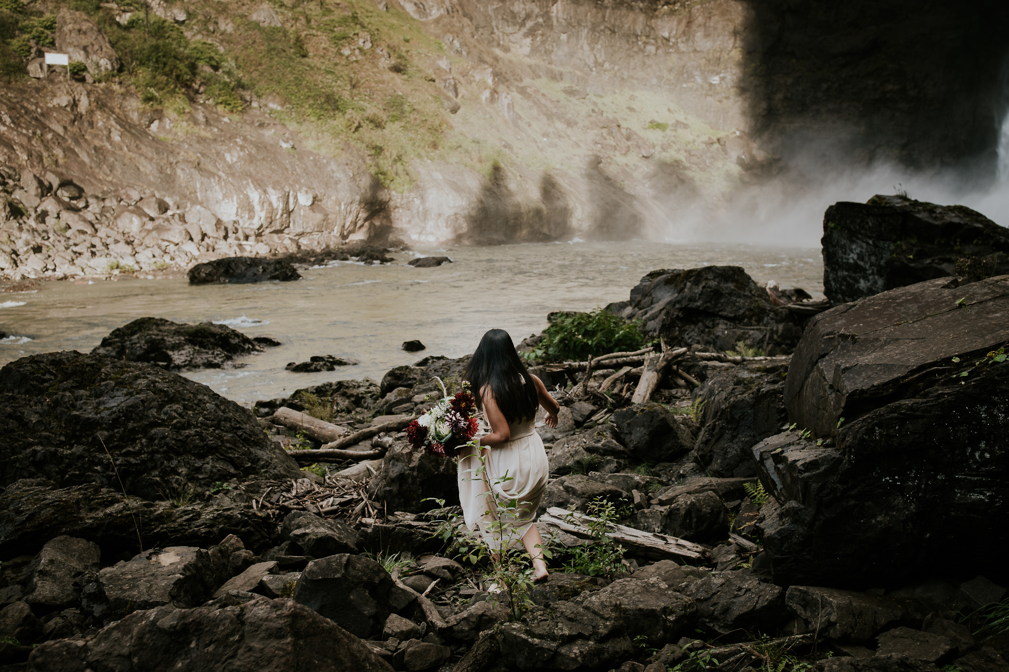 Adventurous bride climbing over rocks holding dress at Snoqualmie Falls